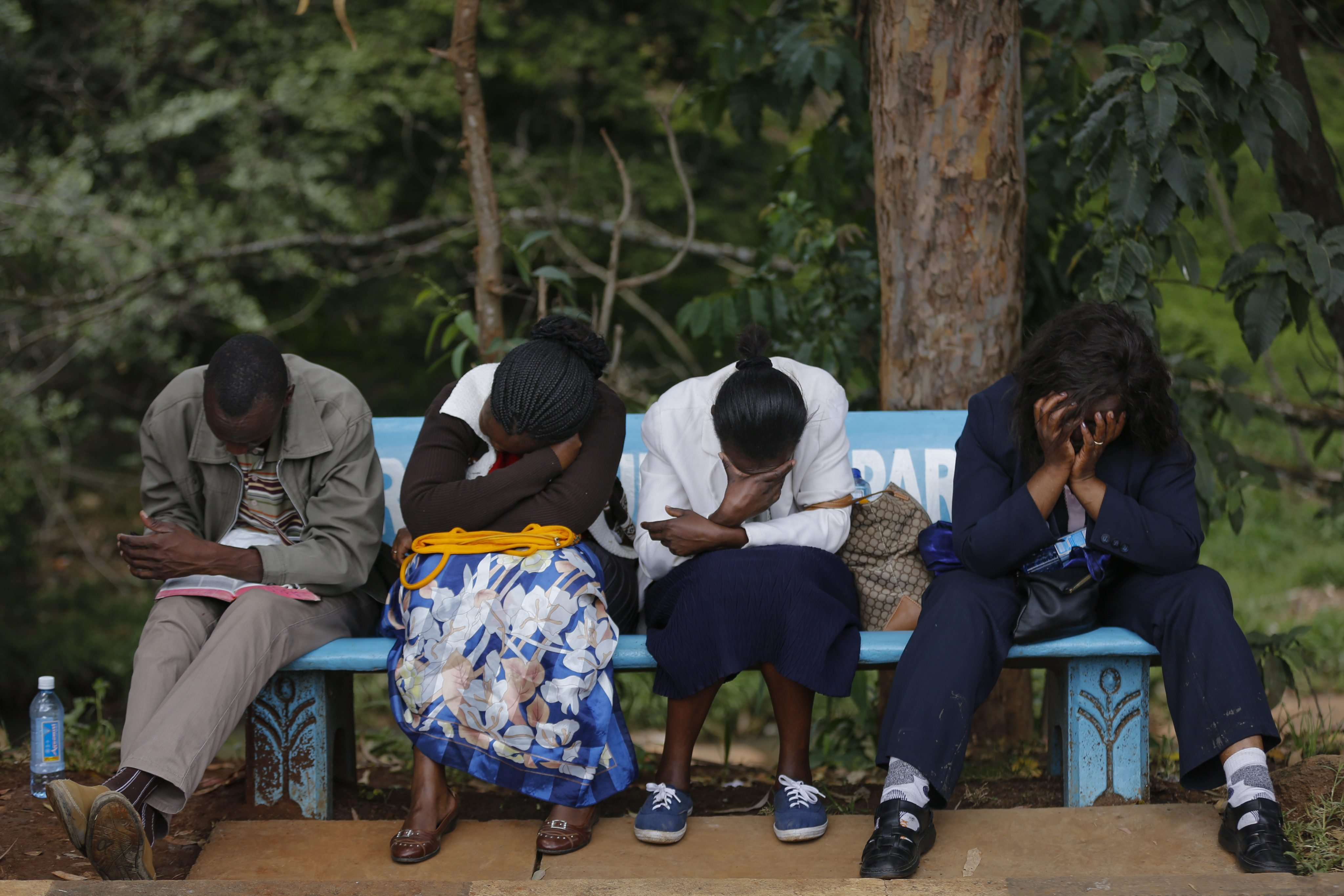 Family members sit on a bench as they wait to view the bodies of their loved ones who had been killed in an attack on Garissa University College, at a mortuary in Nairobi on April 8, 2015.