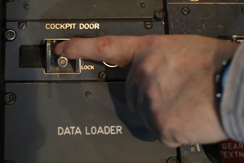 A person moves the switch of the cockpit door locking system inside a flight simulator of an Airbus A320 in Vienna on March 26, 2015.