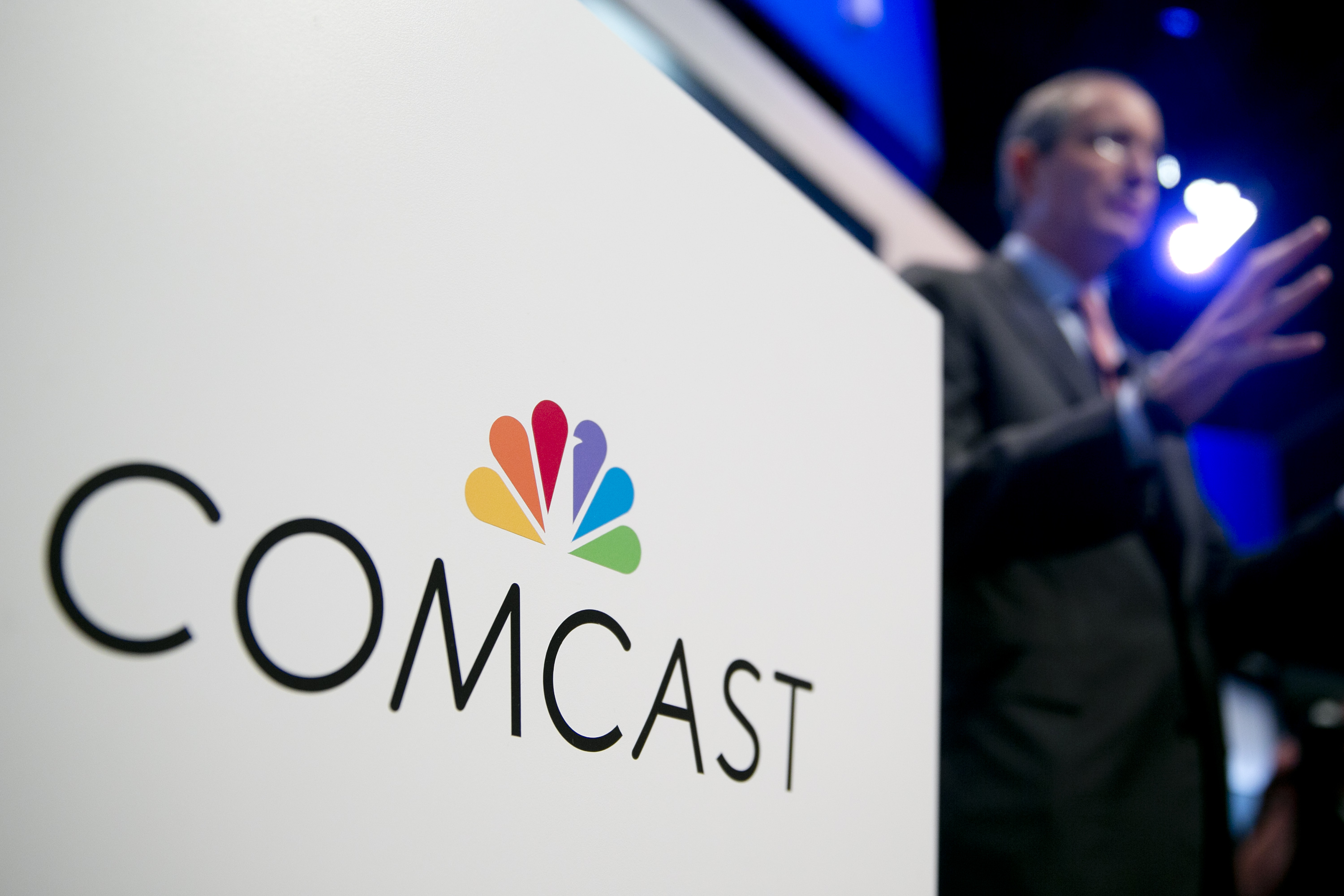 The Comcast Corp. logo is seen as Brian Roberts, chairman and chief executive officer of Comcast Corp. (R) speaks during a news conference in Washington on June 11, 2013.