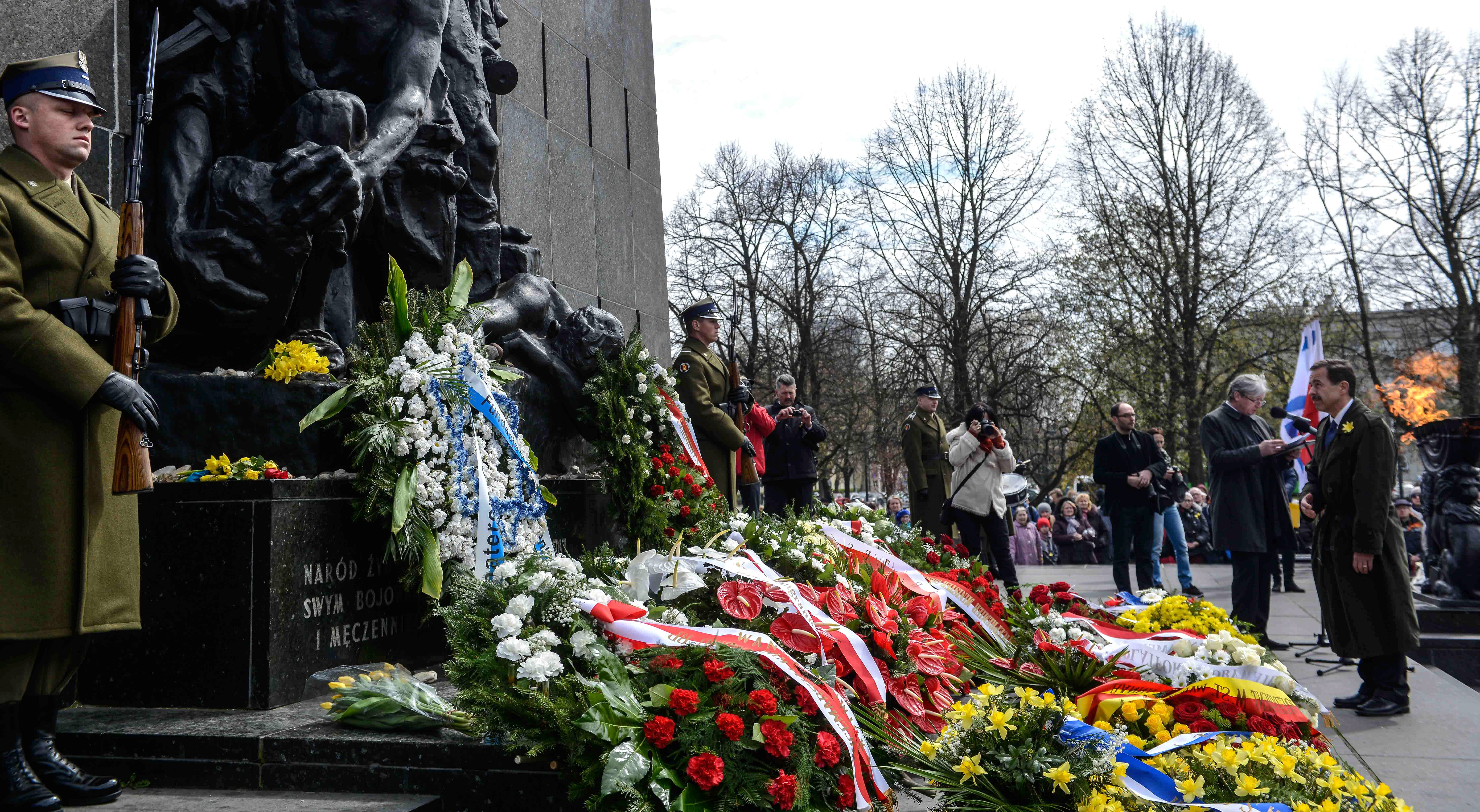 The U.S. ambassador to Poland, Stephen Mull, right, lays flowers at the Monument to the Ghetto Heroes in Warsaw on April, 19, 2015
