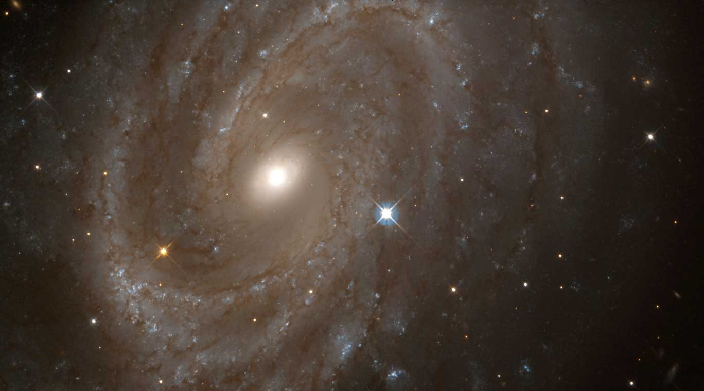 <strong>NGC 4603</strong>:                                   This galaxy is the most distant in which a special class of pulsating stars called Cepheid variables have been found. It is associated with the Centaurus cluster, one of the most massive assemblages of galaxies in the nearby universe. The Local Group of galaxies, of which the Milky Way is a member, is moving in the direction of Centaurus at a speed of more than a million miles an hour under the influence of the gravitational pull of the matter in that direction.                                   <i>Image released on May 25, 1999</i>