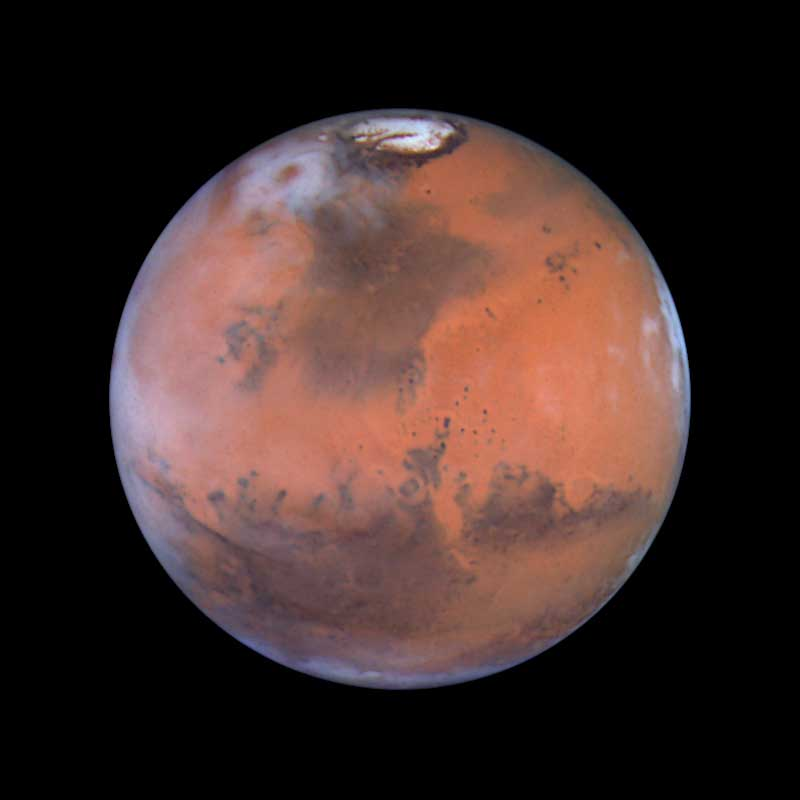 Mars:                               This image is centered near the location of the Pathfinder landing site. Dark sand dunes that surround the polar cap merge into a large, dark region called Acidalia. Below and to the left of Acidalia are the massive Martian canyon systems of Valles Marineris. Early morning clouds can be seen along the left limb of the planet, and a large cyclonic storm composed of water ice is churning near the polar cap.                               Image released on June 30, 1999