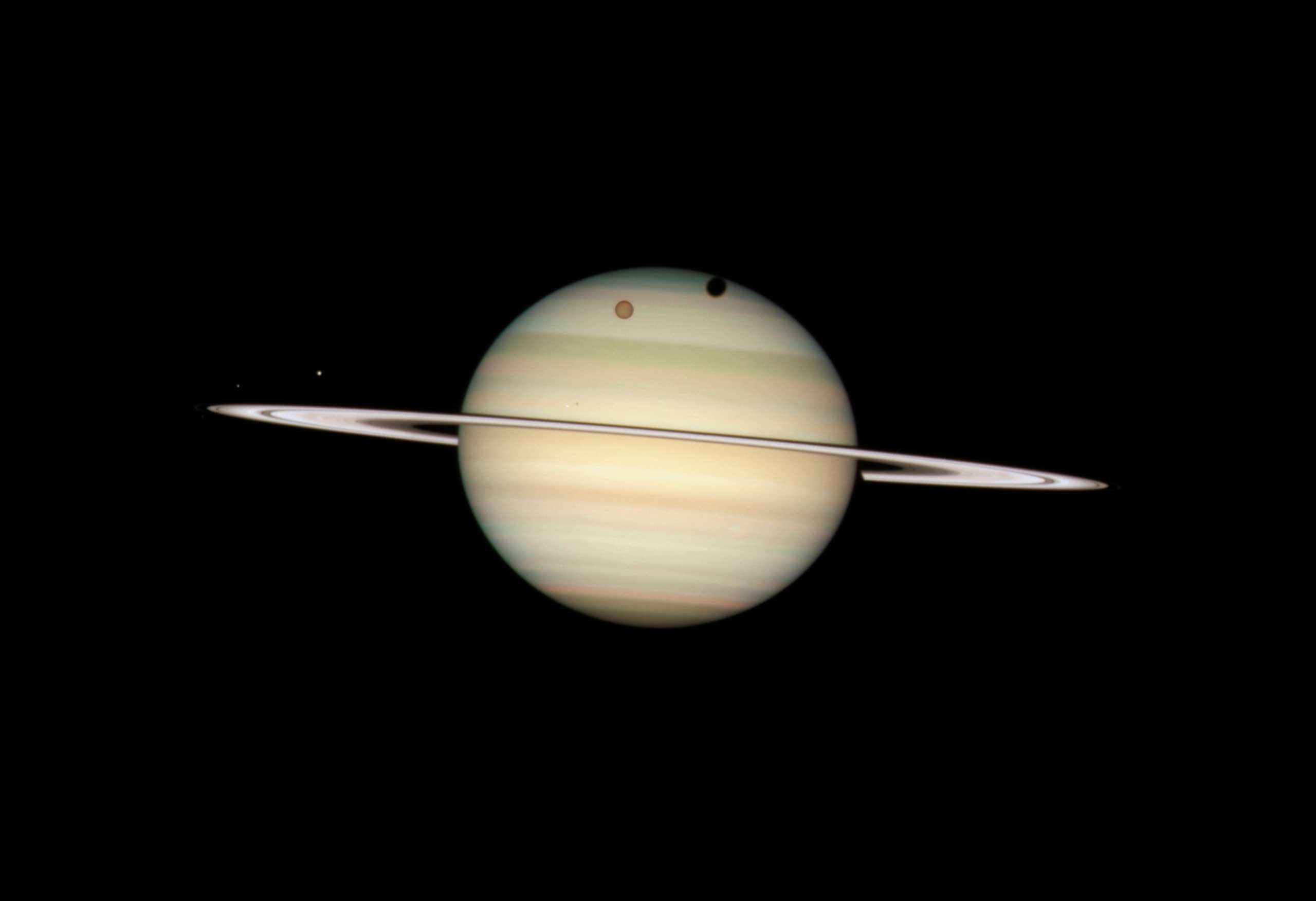 Saturn:                                                              In this photo, Hubble captured the four moons of Saturn passing in front of their parent planet. The giant orange moon Titan casts a large shadow onto Saturn's north polar hood. Below Titan, near the ring plane and to the left is the moon Mimas, casting a much smaller shadow onto Saturn's equatorial cloud tops. Farther to the left, and off Saturn's disk, are the bright moon Dione and the fainter moon Enceladus.                                                              Image released on March 17, 2009