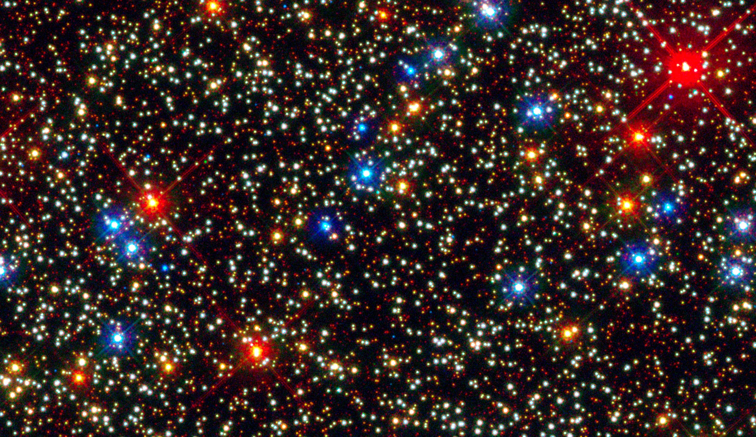 Colorful Stars Inside Globular Star Cluster Omega Centauri:                                                              NASA's Hubble Space Telescope snapped this panoramic view of a colorful assortment of 100,000 stars in the core of a giant star cluster.                               The image reveals a small region inside the massive globular cluster Omega Centauri, which holds nearly 10 million stars. The stars in Omega Centauri are between 10 billion and 12 billion years old. The cluster lies about 16,000 light-years from Earth.                                                              The majority of the stars in the image are yellow-white, like our Sun. These are adult stars that are shining by hydrogen fusion. Toward the end of their normal lives, the stars become cooler and larger. These late-life stars are the orange dots in the image.                                                               Even later in their life cycles, the stars continue to cool down and expand in size, becoming red giants. These bright red stars swell to many times larger than our Sun's size and begin to shed their gaseous envelopes.                               After ejecting most of their mass and exhausting much of their hydrogen fuel, the stars appear brilliant blue. Only a thin layer of material covers their super-hot cores. These stars are desperately trying to extend their lives by fusing helium in their cores. At this stage, they emit much of their light at ultraviolet wavelengths.                               When the helium runs out, the stars reach the end of their lives. Only their burned-out cores remain, and they are called white dwarfs (the faint blue dots in the image).                                                               Image released on Oct. 26, 2010.