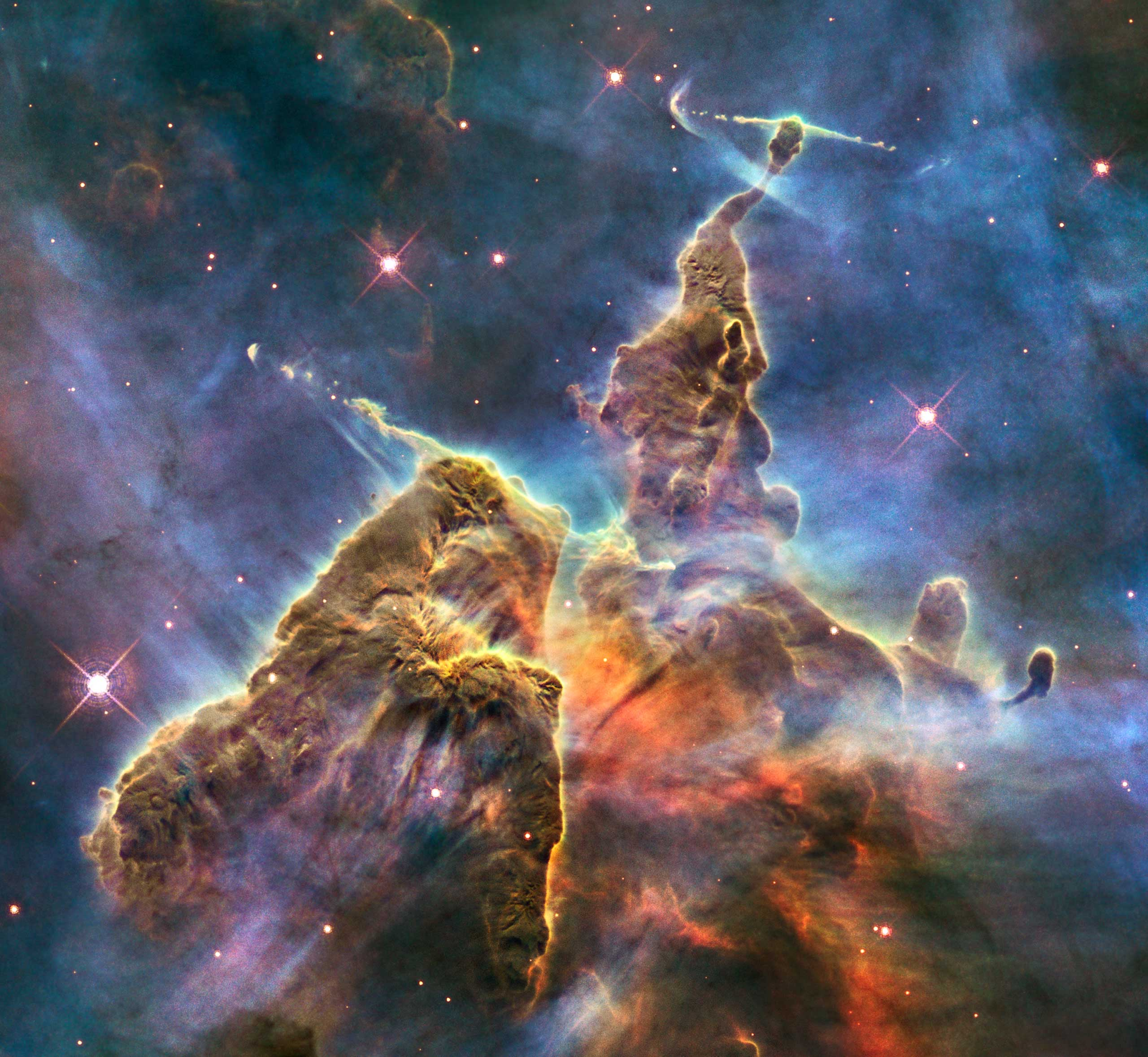 <strong>Mystic Mountain</strong>:                                                                      This image captures the chaotic activity atop a three-light-year-tall pillar of gas and dust that is being eaten away by the brilliant light from nearby bright stars. The pillar is also being assaulted from within, as infant stars buried inside it fire off jets of gas that can be seen streaming from towering peaks. This turbulent cosmic pinnacle lies within the Carina Nebula, located 7,500 light-years away in the southern constellation Carina.                                                                       <i>Image released on April 22, 2010</i>