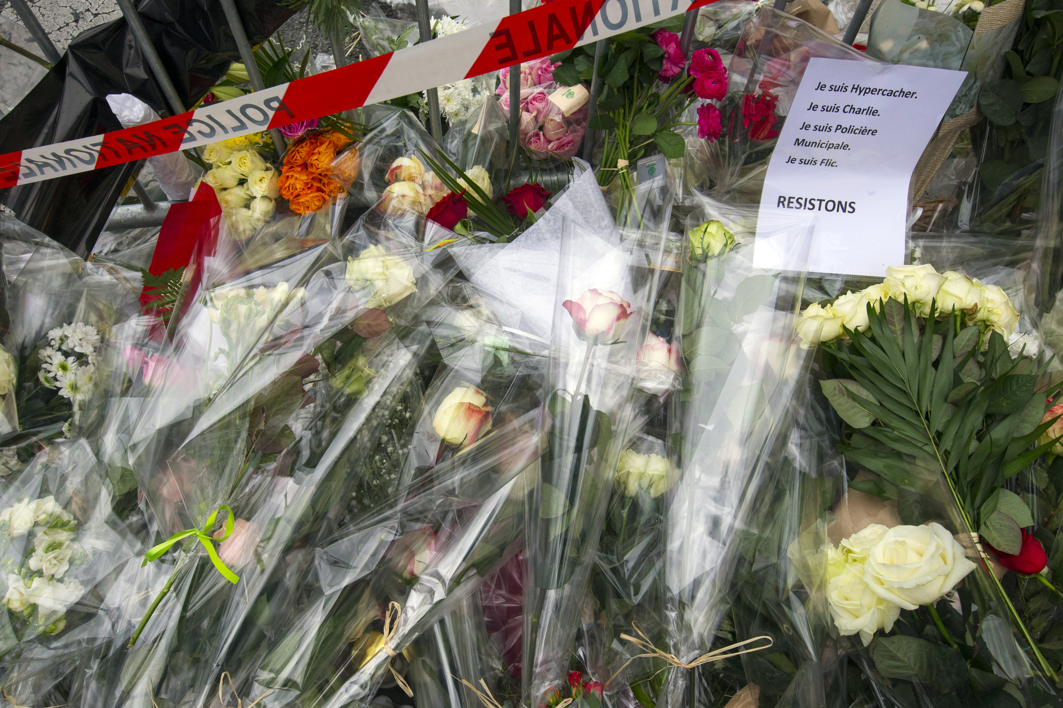A sign reading  I am Hypercacher, I am Charlie and I am police officer, we must resist  is placed among flowers outside the Hyper Cacher kosher supermarket near Porte de Vincennes in eastern Paris, on Jan. 10, 2015.
