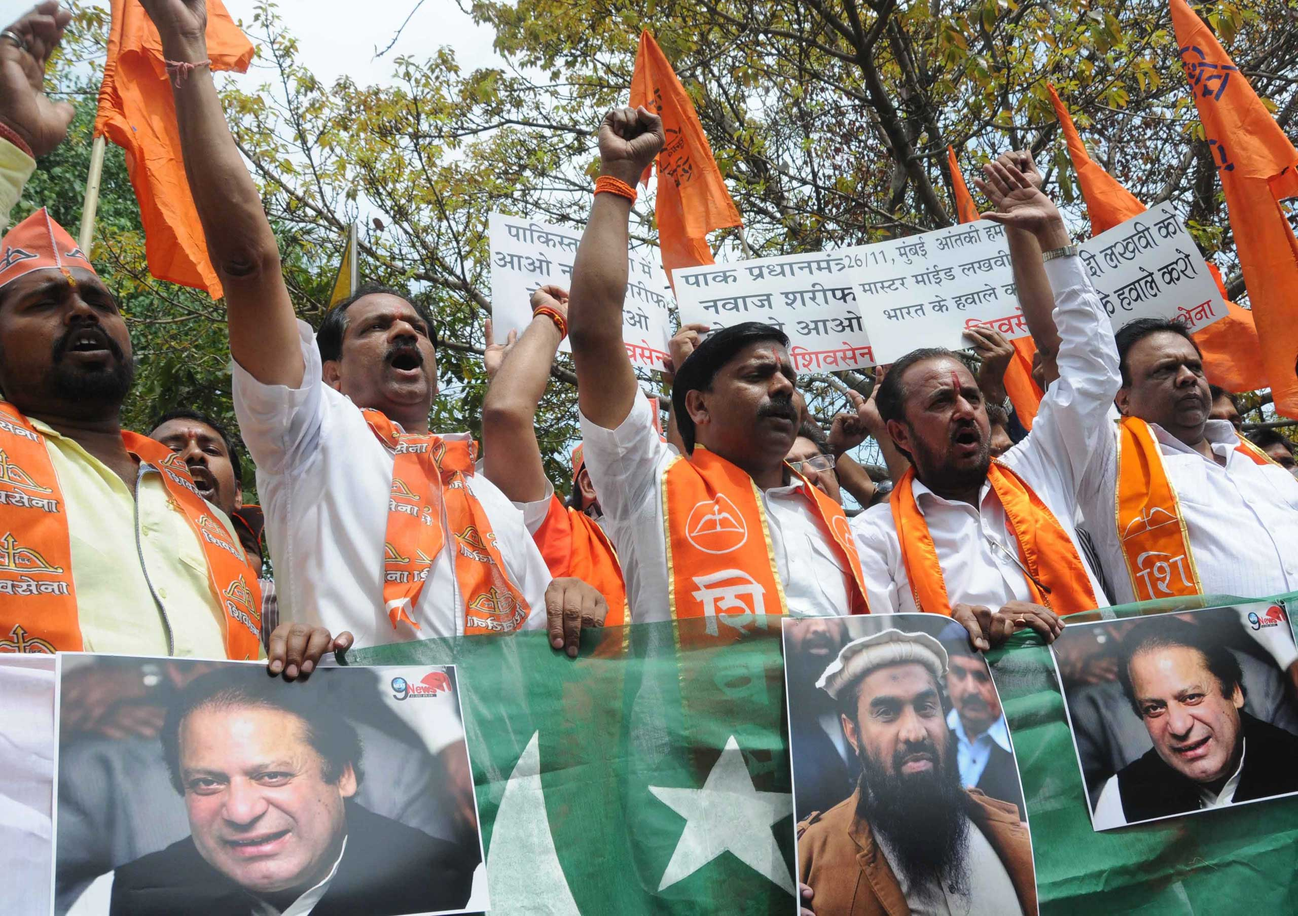 Activists of India's right-wing Shiv Sena party shout slogans before they burnt posters of Pakistani Prime Minister Nawaz Sharif and Zaki-ur-Rehman Lakhvi (C-bottom), alleged mastermind of the 2008 Mumbai attacks during a protest against Zaki-ur-Rehman's release, in New Delhi, on April 11, 2015.