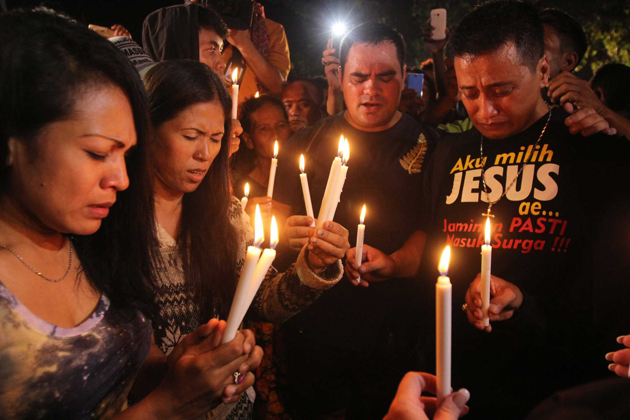 People hold candles to pray for death-row prisoners at Wijayapura port in Cilacap, Indonesia on April 29, 2015.