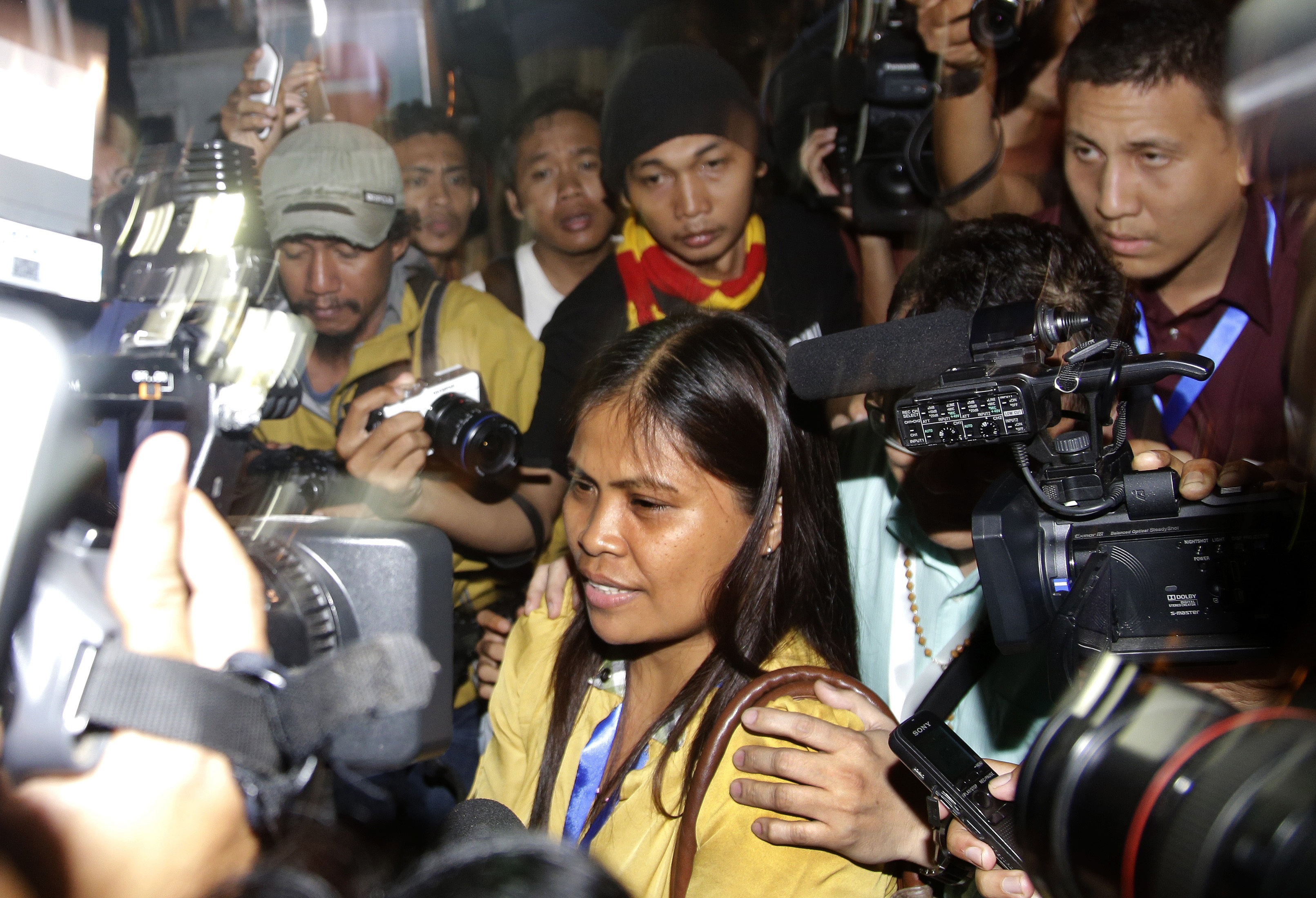 Marites Veloso, front center, sister of Filipina migrant worker on death row for drug offenses Mary Jane Veloso, is surrounded by media at Wijayapura port in Cilacap, Indonesia, after visiting her sister on April 29, 2015