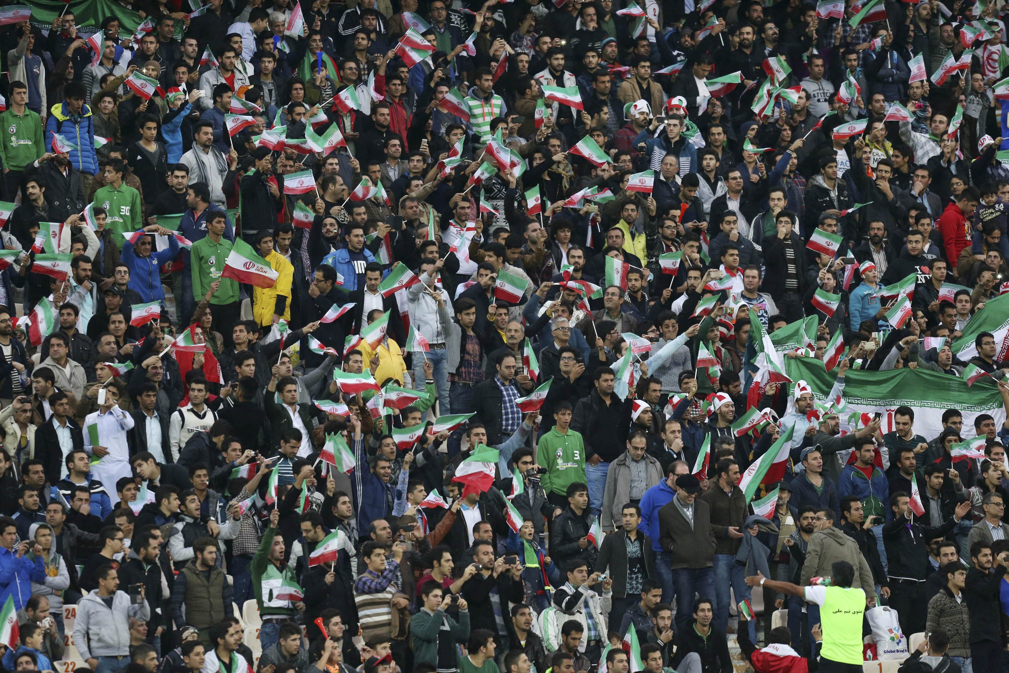 Iranian soccer supporters wave their country's flag following a friendly match at the Azadi, (freedom) stadium in Tehran, Iran on Nov. 18, 2014.