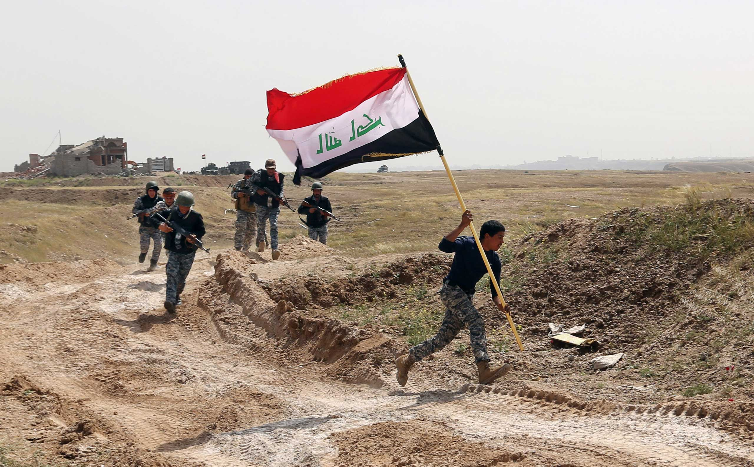 A member of the Iraqi security forces runs to plant the national flag as they surround Tikrit during clashes to regain the city from Islamic State militants, 80 miles north of Baghdad, Iraq, March 30, 2015.