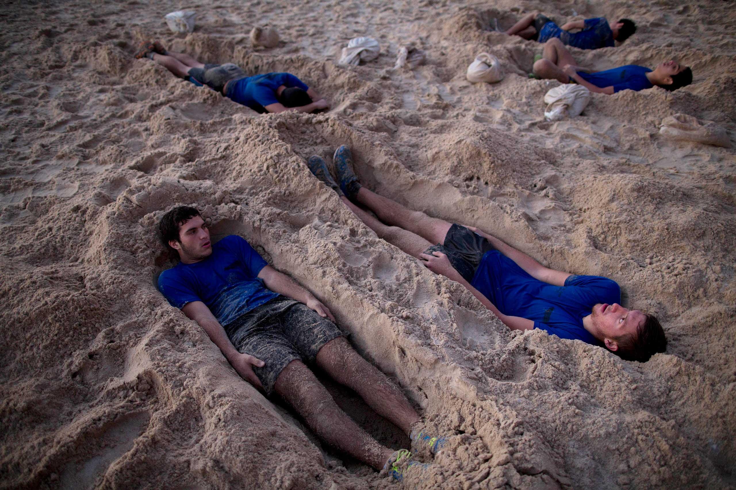 High-school seniors preparing to join the Israeli military later this year lie in foxholes during training in Shefayim, central Israel, March 5, 2015.