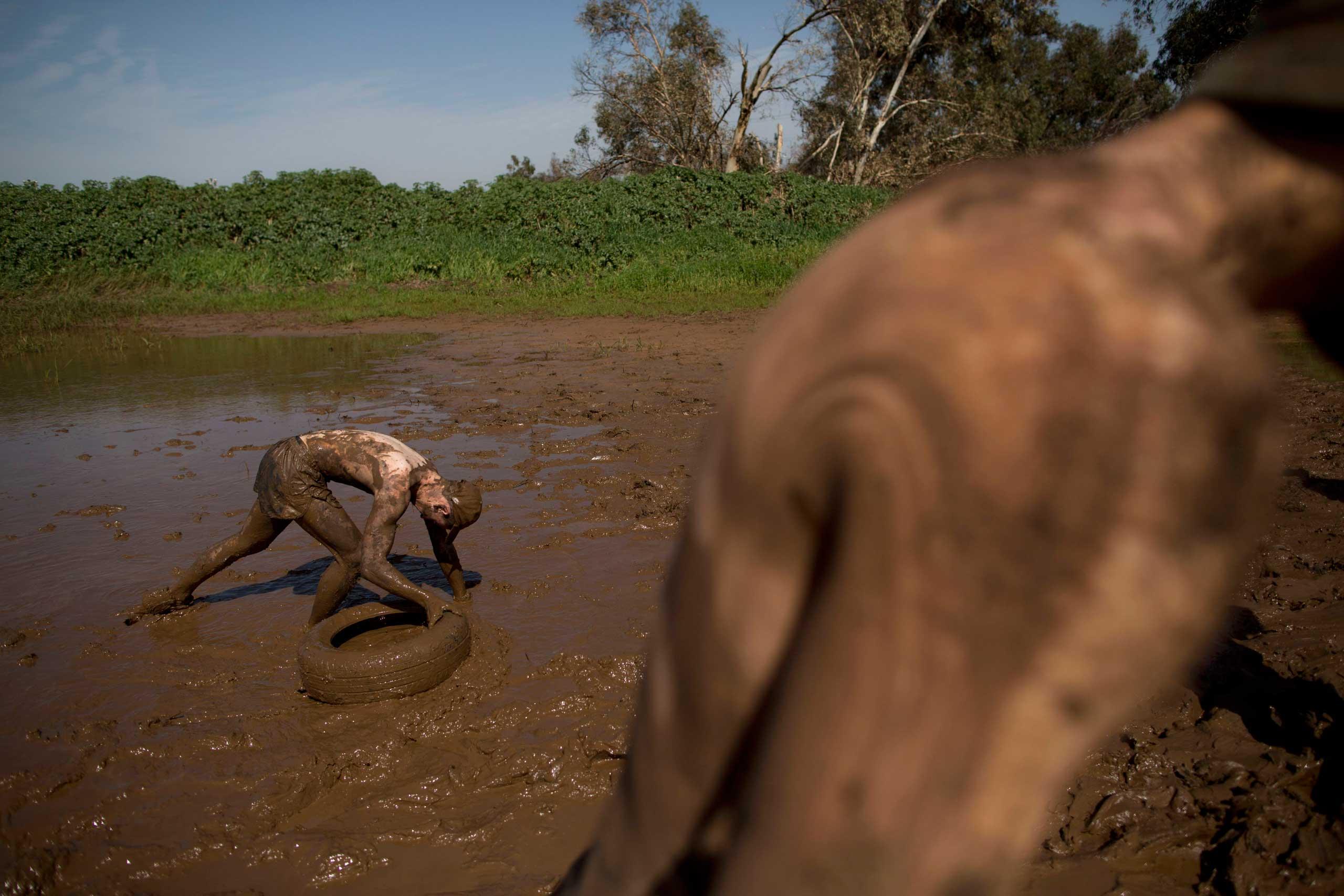 A high-school senior  drags a tire through mud during training near Yakum, central Israel, Feb. 27, 2015.