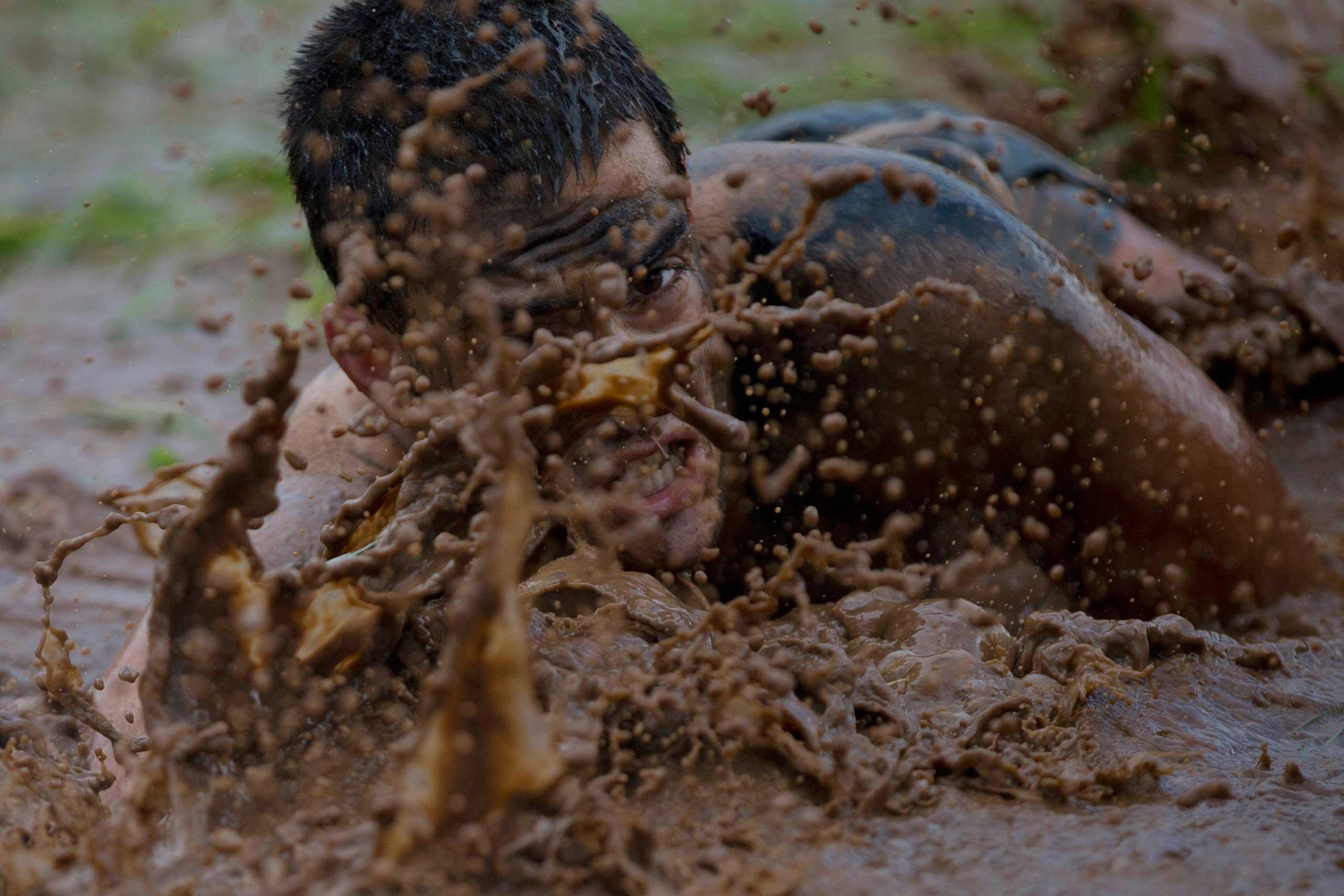 A high-school senior crawls through mud during an exercise near Yakum, central Israel, Feb. 13, 2015.