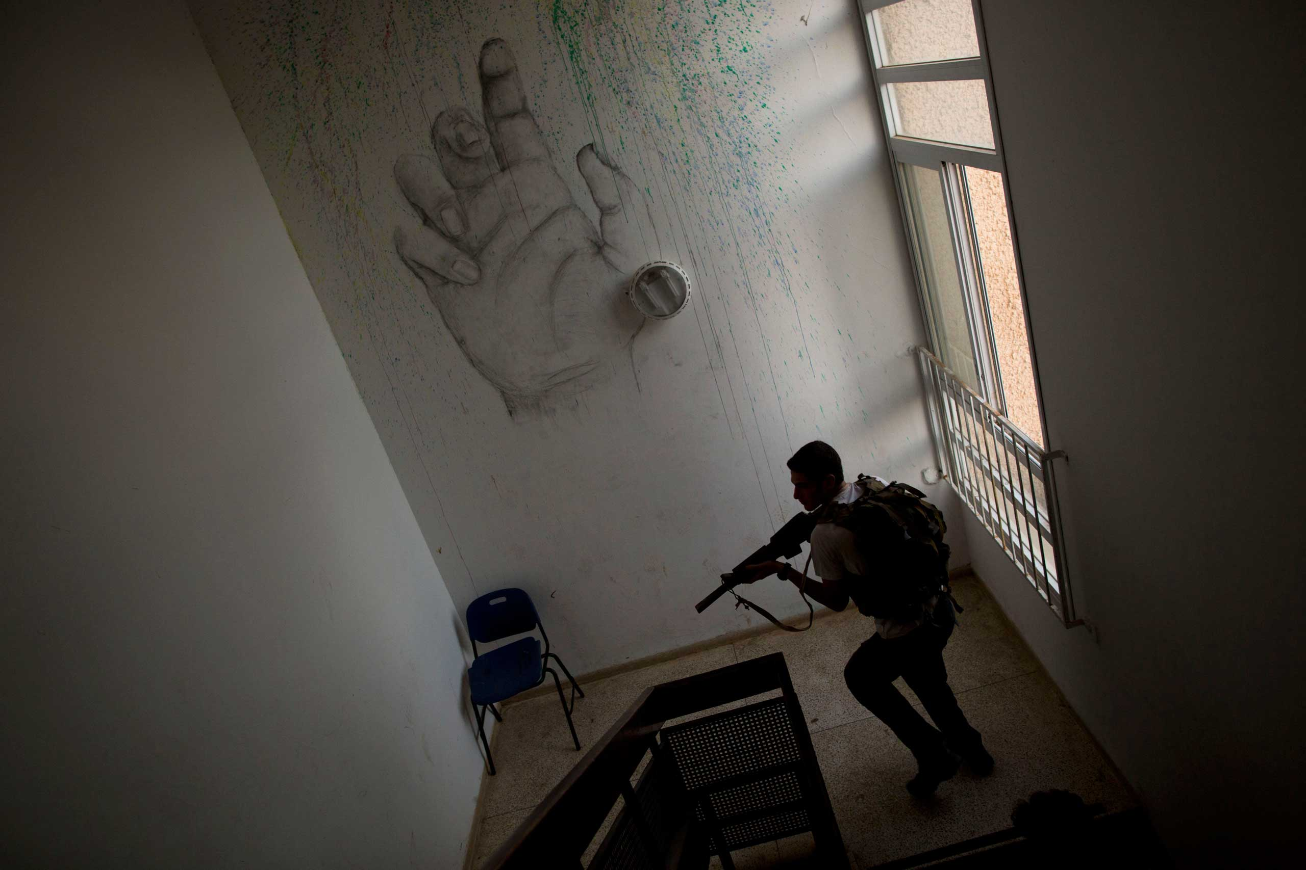 A high-school senior preparing to join the Israeli military participates in an urban fighting drill in Kibbutz Mizra, northern Israel, March 24, 2015.