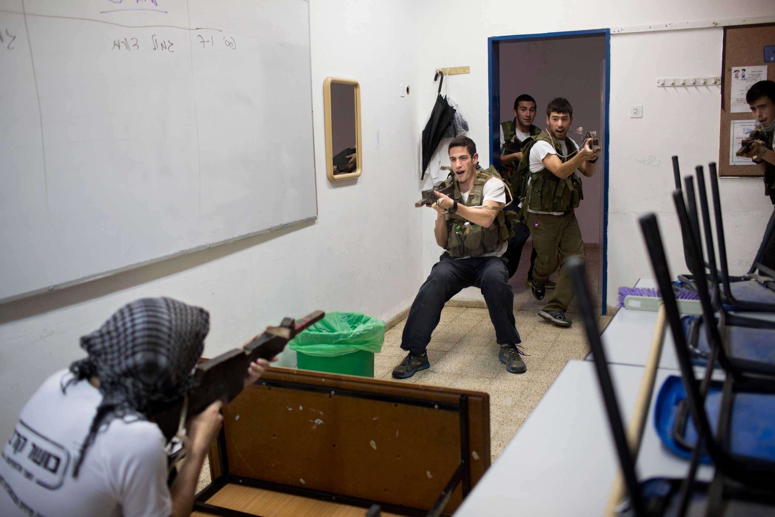 High-school seniors preparing to join the Israeli military participate in an urban fighting drill in Kibbutz Mizra, northern Israel, March 24, 2015.