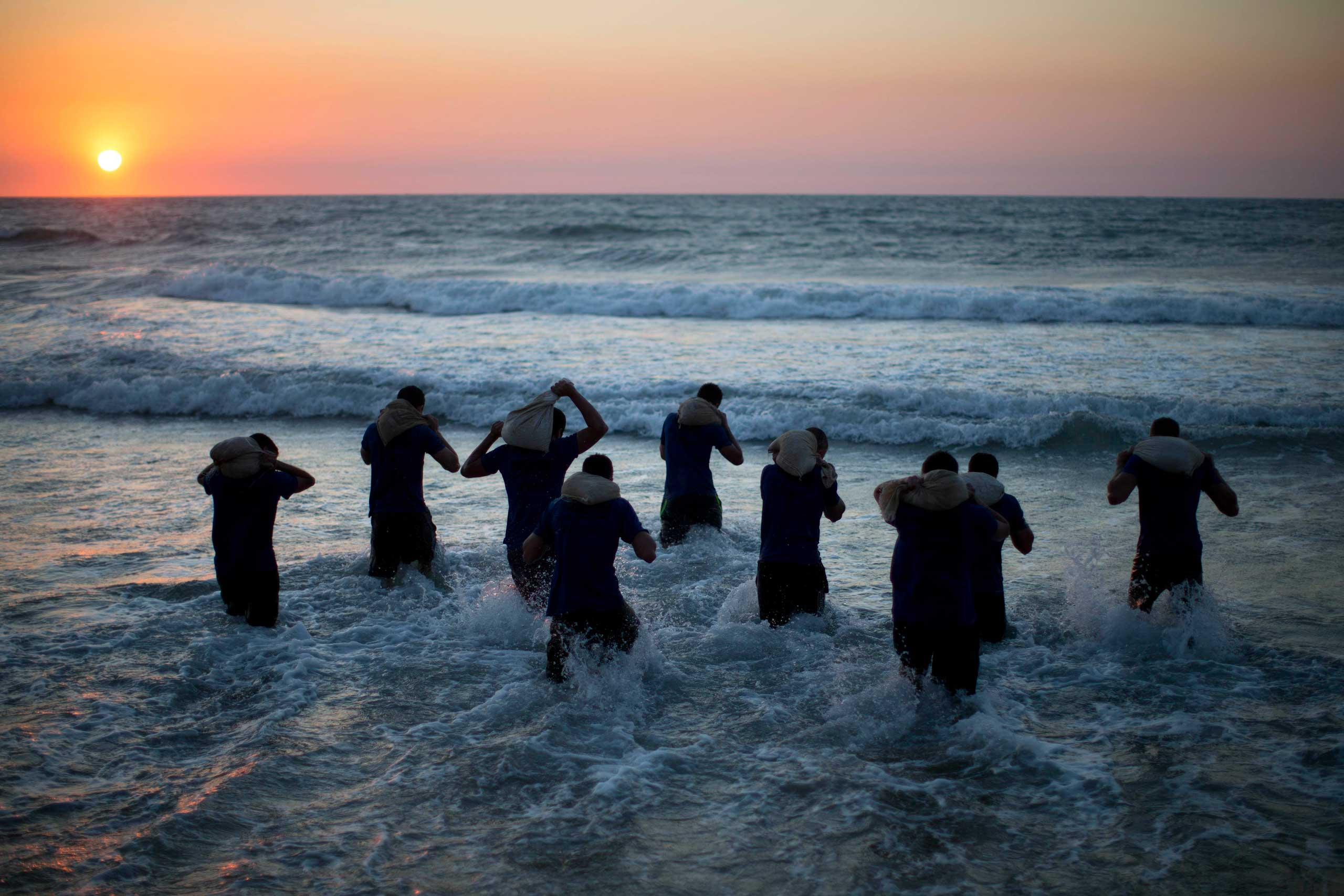 High-school seniors walk into the sea carrying weighted bags the during military combat fitness training in Shefayim, central Israel, March 5, 2015.
