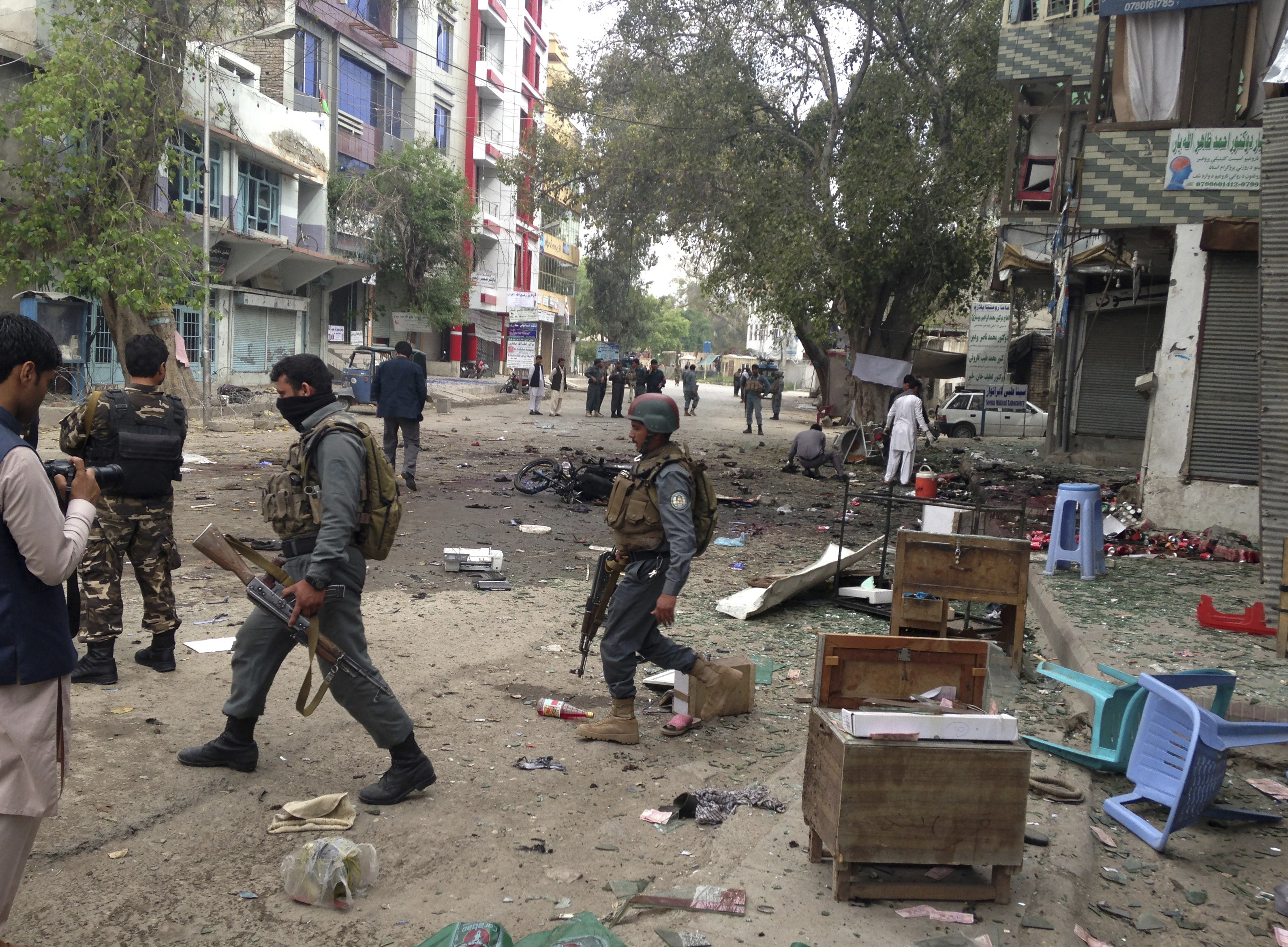 Afghan security forces members inspect the site of a suicide attack near a new Kabul Bank in Jalalabad, east of Kabul, Afghanistan, April, 18, 2015.