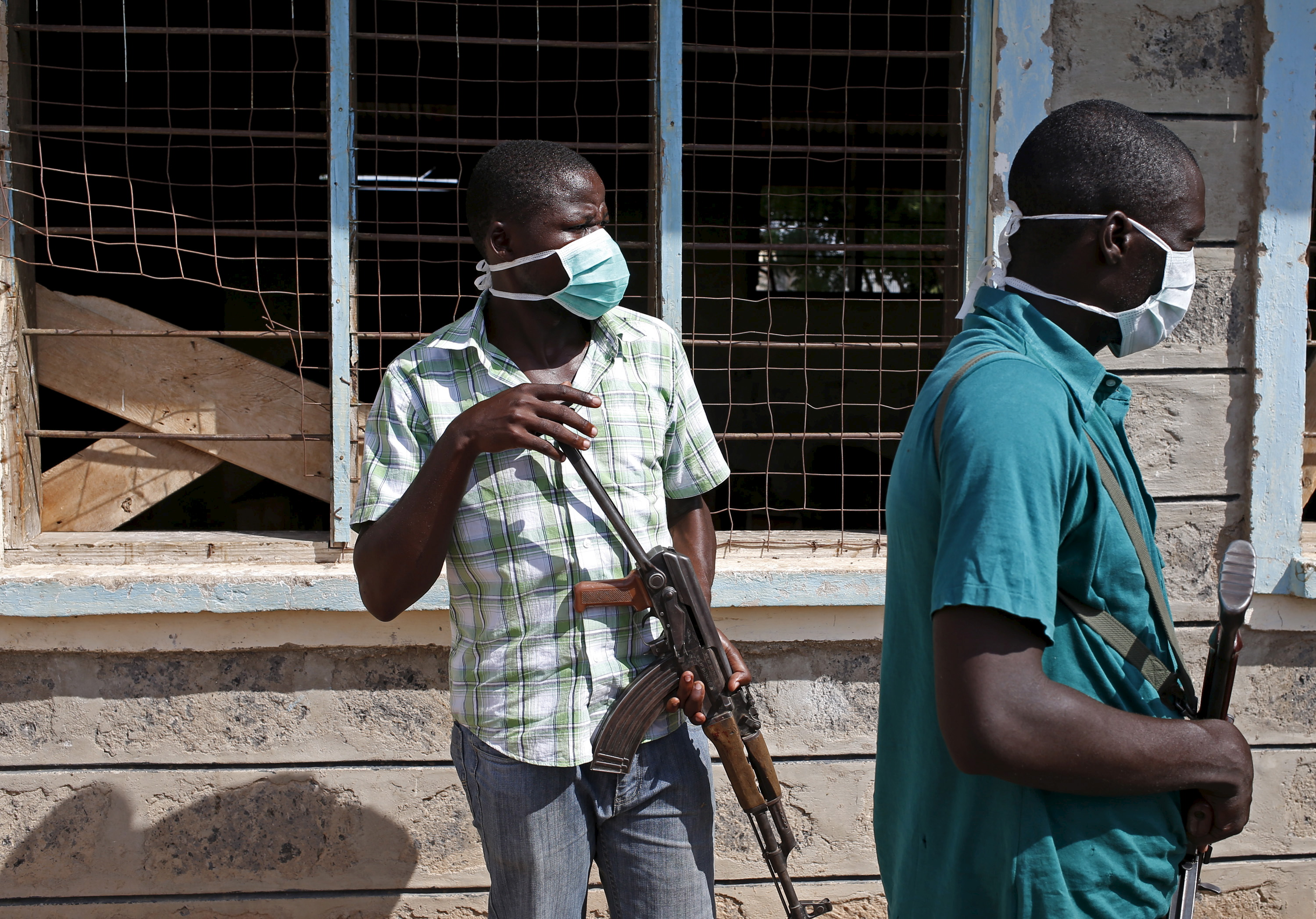 Plainclothes policemen stand in front of a crowd which came to see bodies of suspected Garissa University College attackers in a school compound in Garissa, Kenya on April 4, 2015.