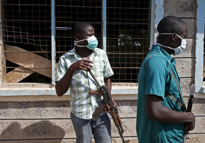Plainclothes policemen stand in front of a crowd which came to see bodies of suspected Garissa University College attackers in a school compound in Garissa