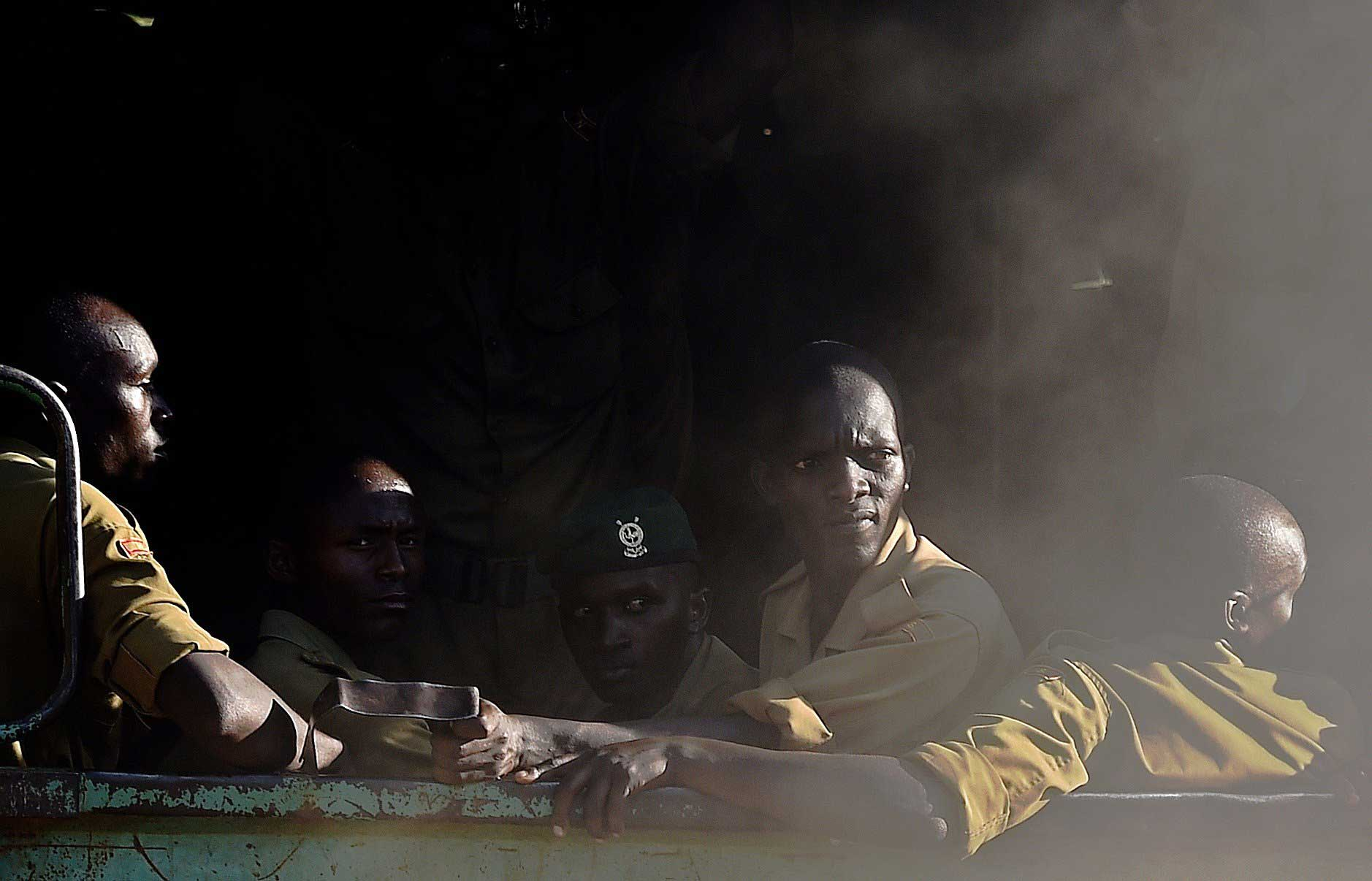 Members of Kenya's police force look out from the back of a truck as it enters the university campus of the northeastern town of Garissa on April 3, 2015.