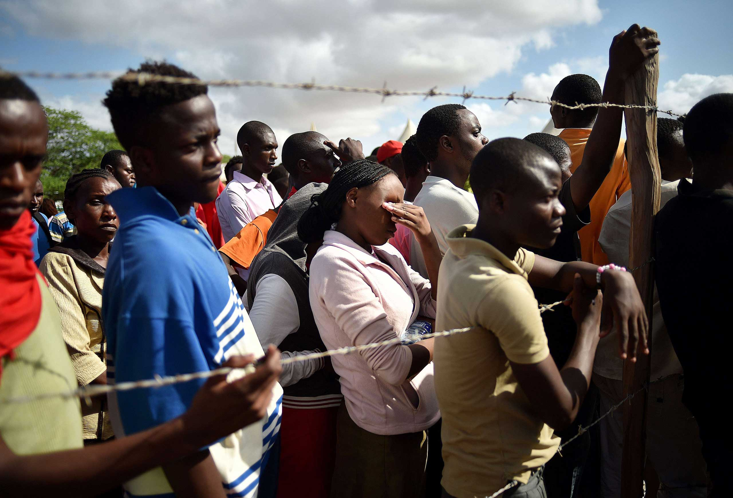 Students evacuated from Garissa University College listen to an address by Interior Minister for Security Joseph Ole Nkaissery before they are transported to their home regions from a holding area on April 3, 2015.