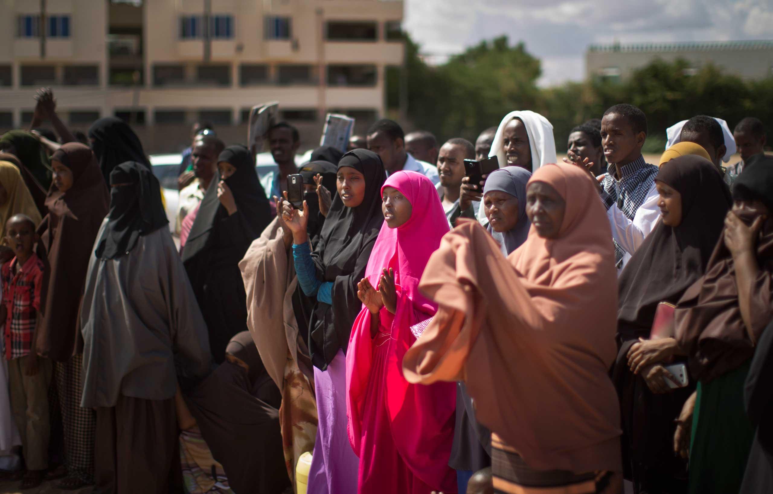 Kenyan Muslim women and men applaud as a women's representative denounces the latest attack by al-Shabab gunmen, at a public meeting in Garissa, Kenya, on Apr. 3, 2015.