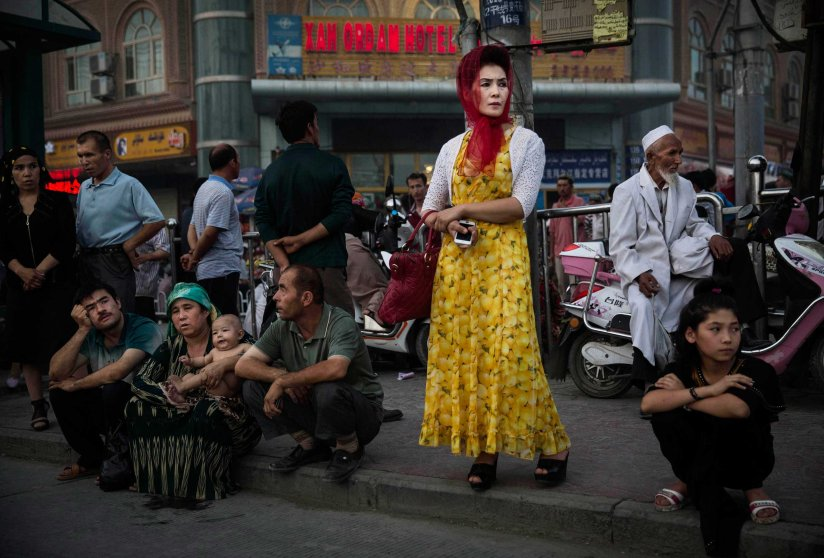 Uighurs wait at a bus stop in old Kashgar, Xinjiang Province, China, July 27, 2014.