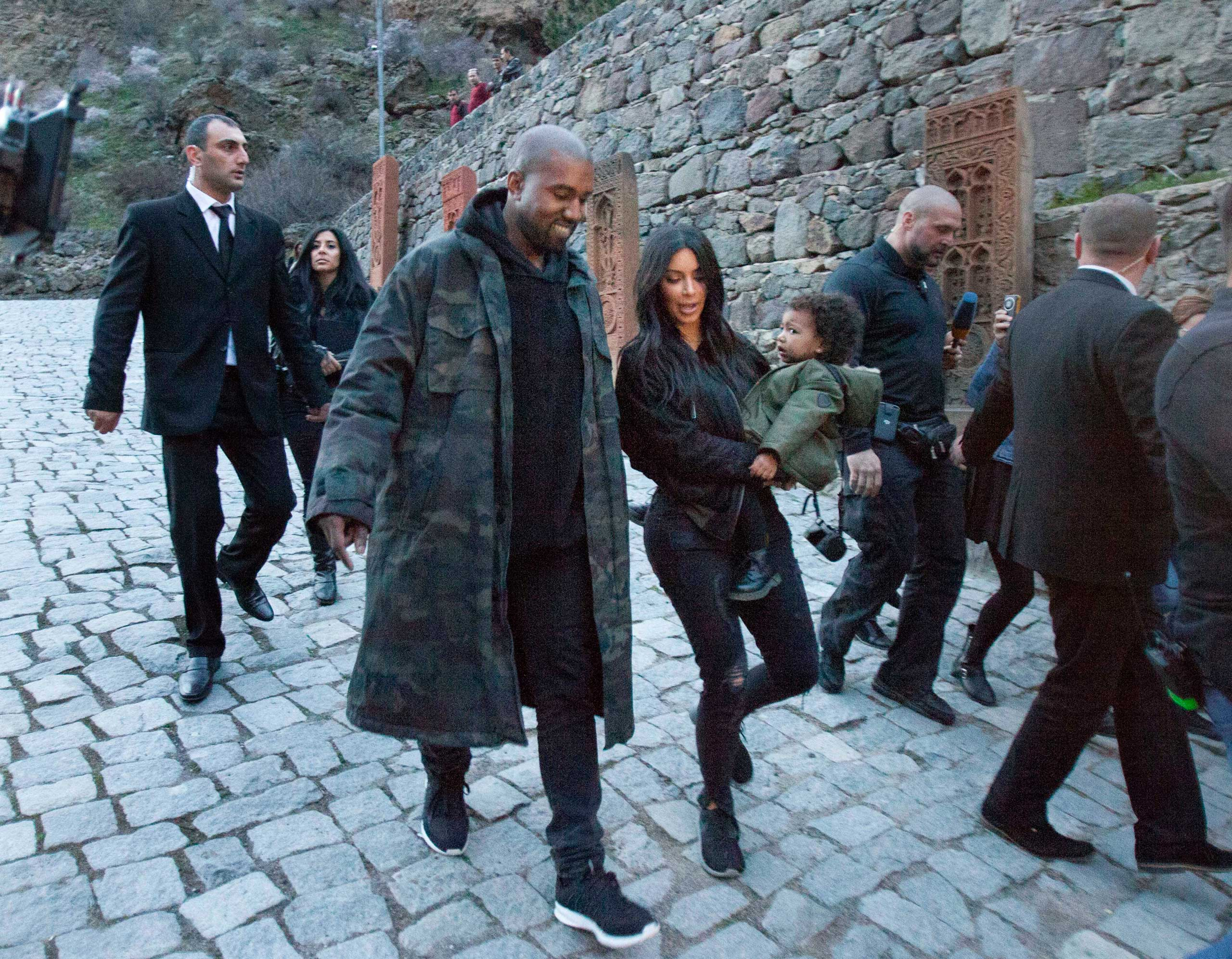 U.S. TV personality Kim Kardashian, center, carriers daughter North as she walks alongside her husband Kanye West visit the Geghard Monastery near Goght, Armenia, April 9, 2015.
