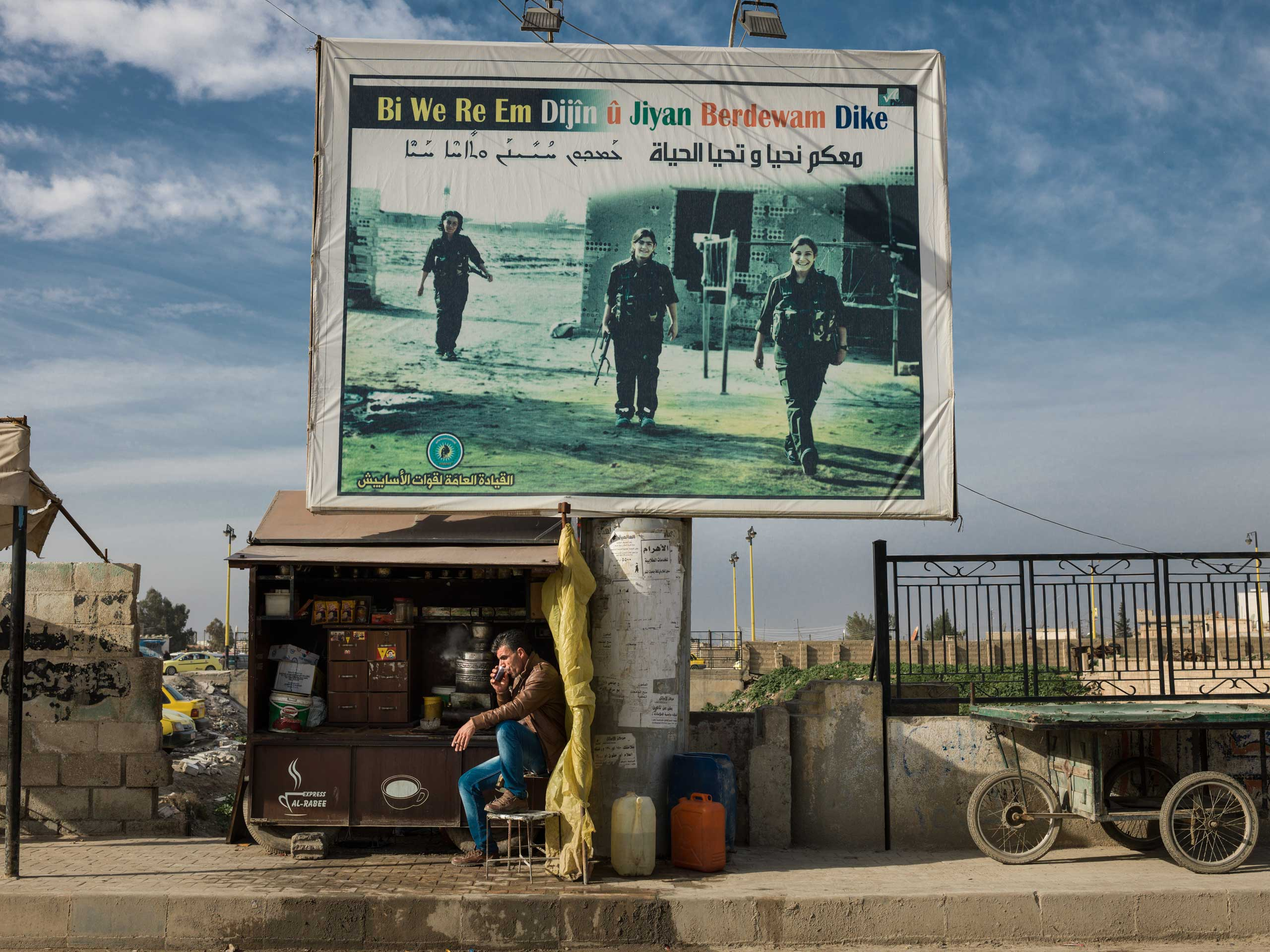 "A  billboard showing fallen YPJ solders, reading, ""With you we live on and life continues."""