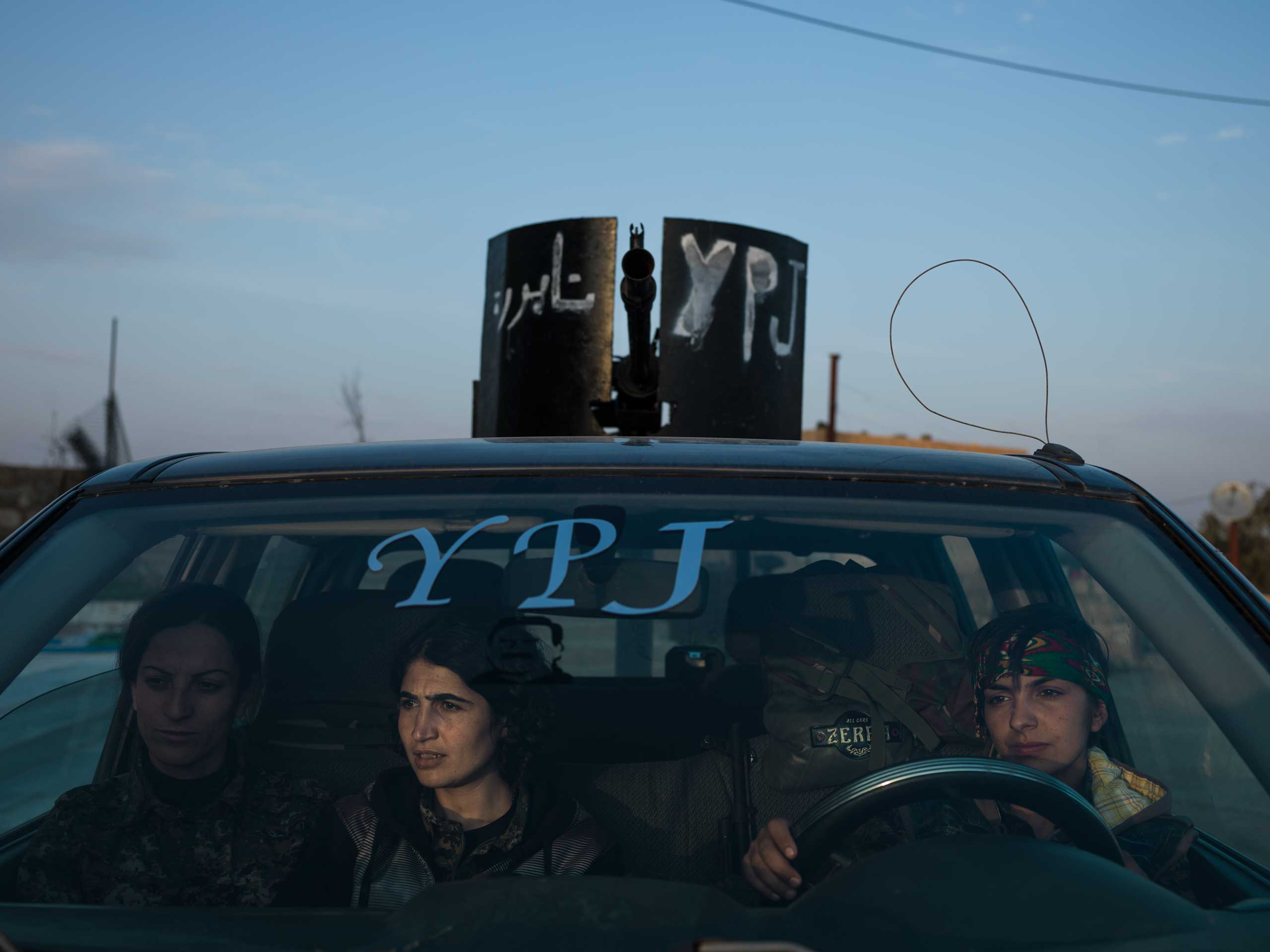 Three YPJ fighters sit in an armed vehicle at their base in eastern Syria, days after returning from the front.