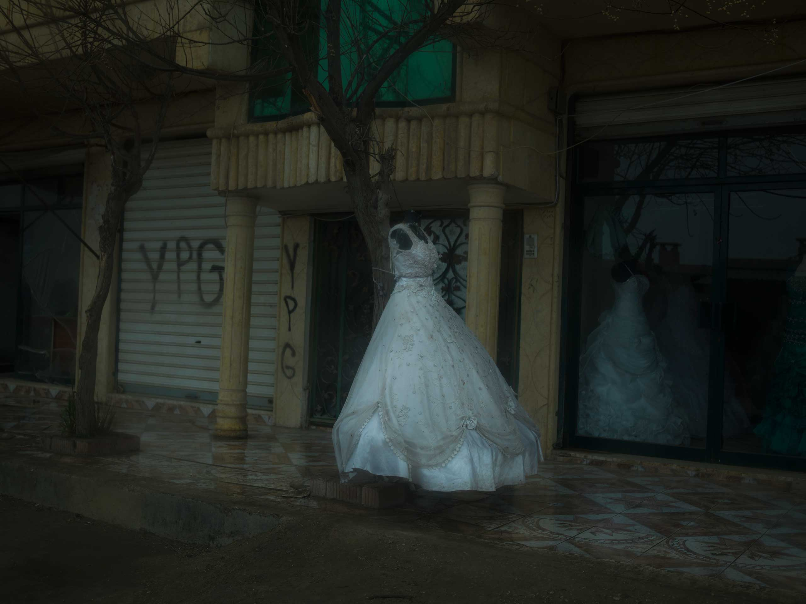 A wedding dress outside a bridal shop in a town near Qamishlou, Syria. YPG graffiti can be seen on the walls of adjacent buildings. YPJ and YPG members are neither allowed to marry, nor can they have sexual relationships, according their ideology.