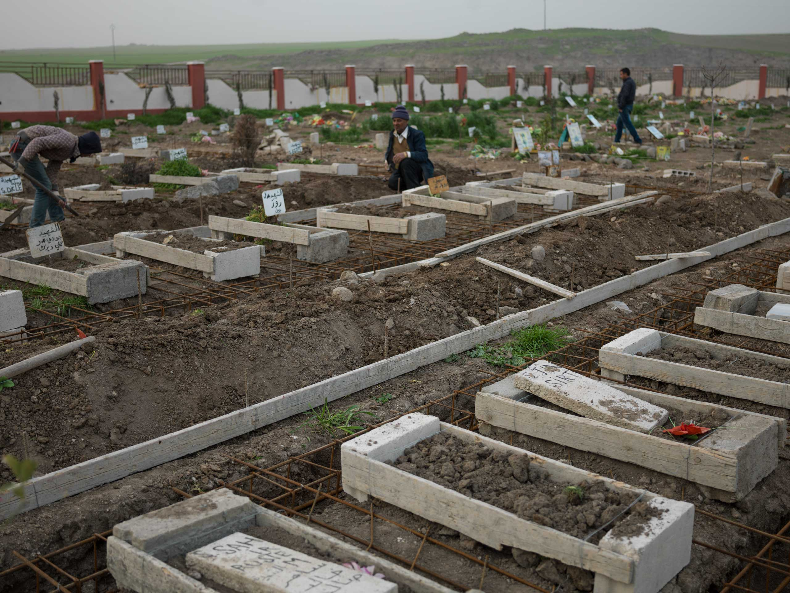 in Syria, graves of YPJ members who were killed fighting ISIS. In the foreground, female fighters are buried together.