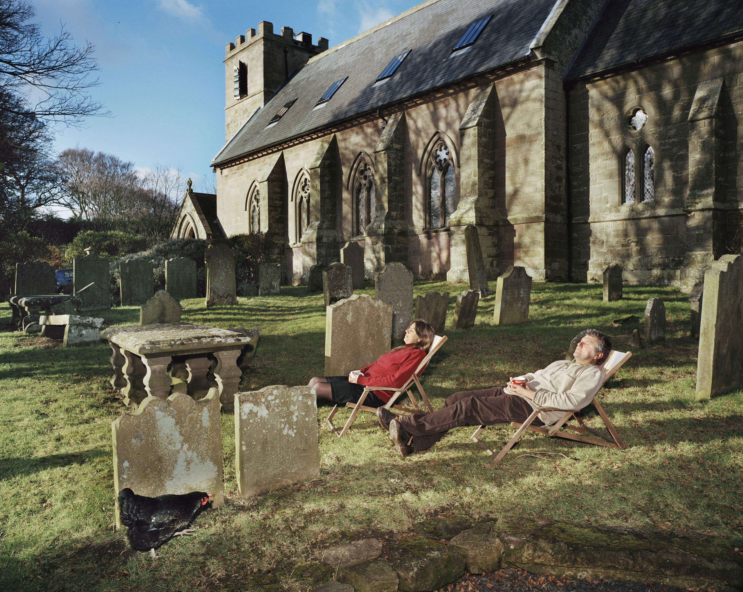 England, Kyloe, 2010 Church House. Ian Bottomley and his partner, Sally Onions, take in the sun in the graveyard of their home, a converted 1792 church.