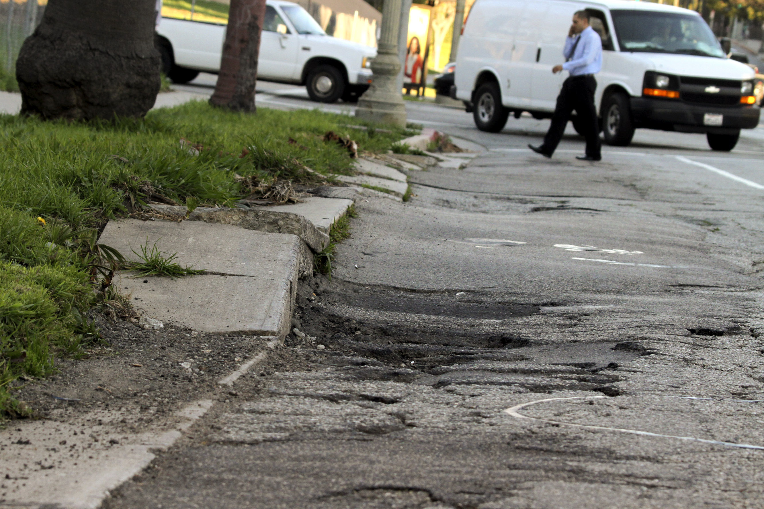 A pedestrian crosses the street past potholes and broken asphalt on Wilshire Boulevard in Los Angeles, California, U.S., on Friday, Jan. 21, 2011