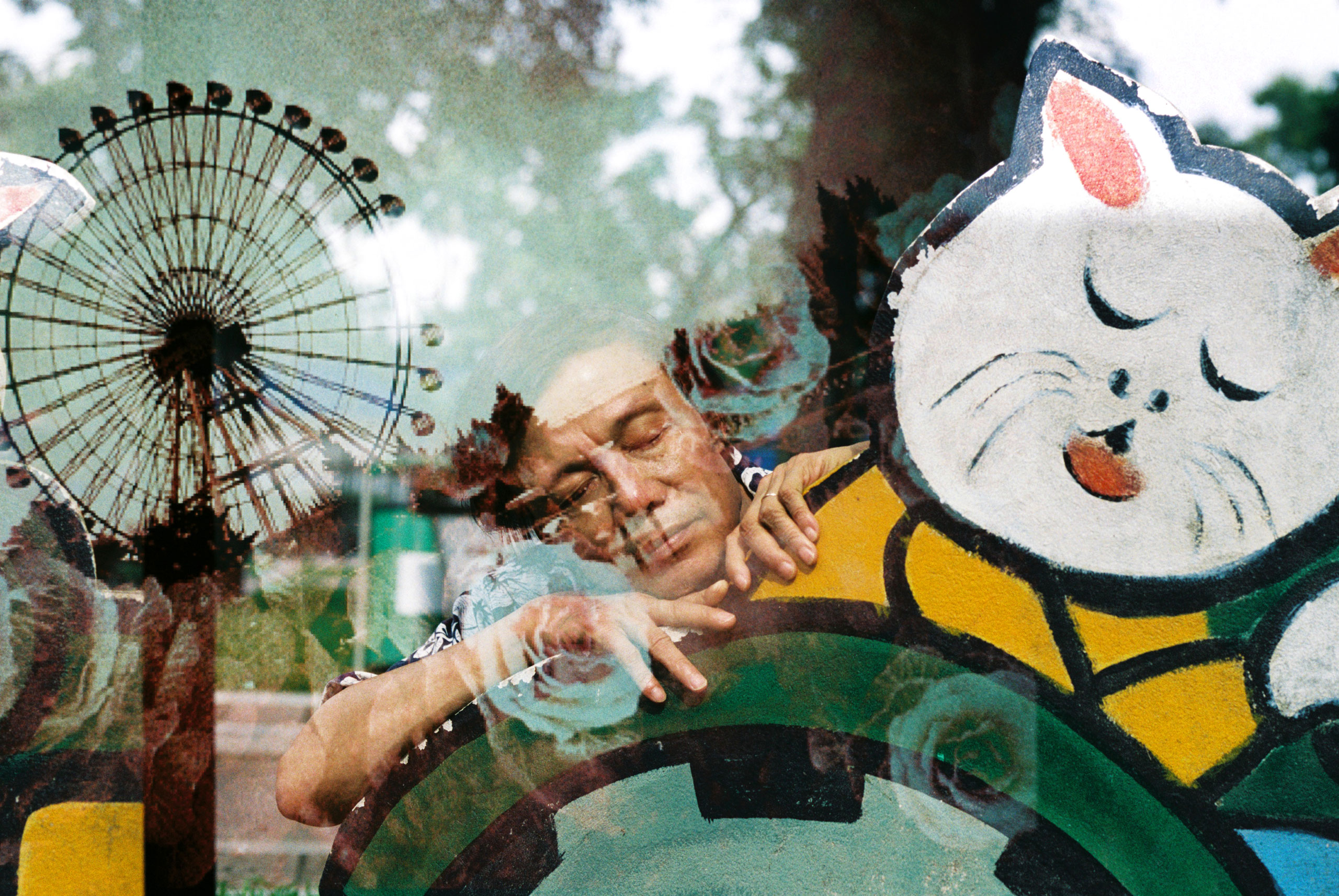 An image of my father resting on a cardboard in Lenin Park, overlaid by an image of an ferris wheel at the water park of Hanoi, August, 2013.