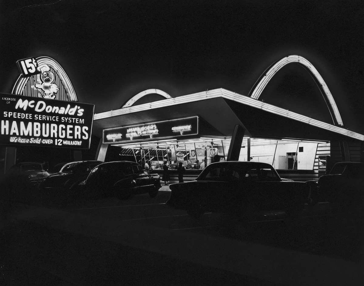 The first McDonald's fast food franchise with its neon arches illuminated at night, Des Plaines, Ill., circa 1955