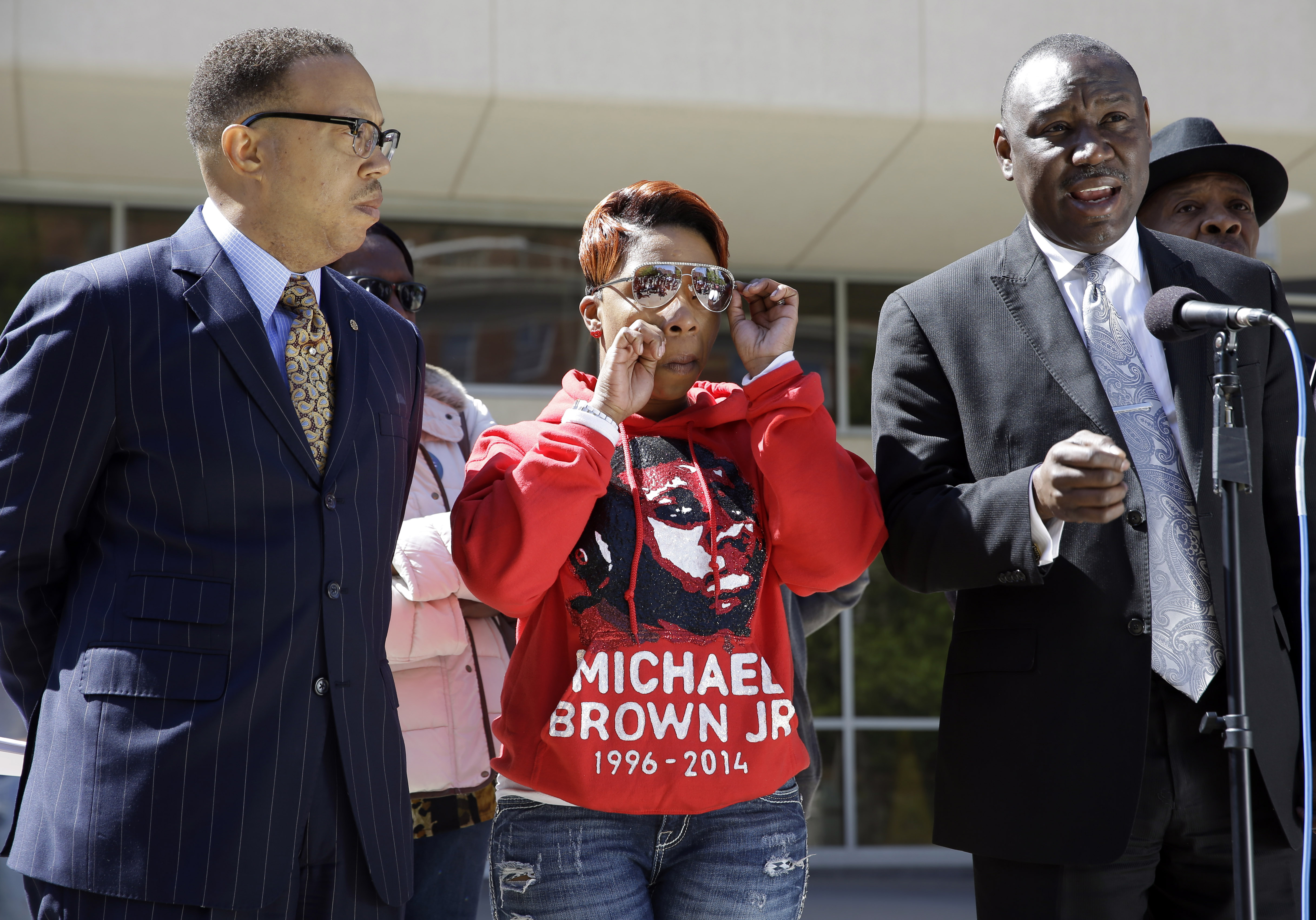Lesley McSpadden, mother of Michael Brown, wipes her eye as she is flanked by her attorneys Anthony D. Gray, left, and Benjamin L. Crump, right, during a news conference April 23, 2015, in Clayton, Mo.