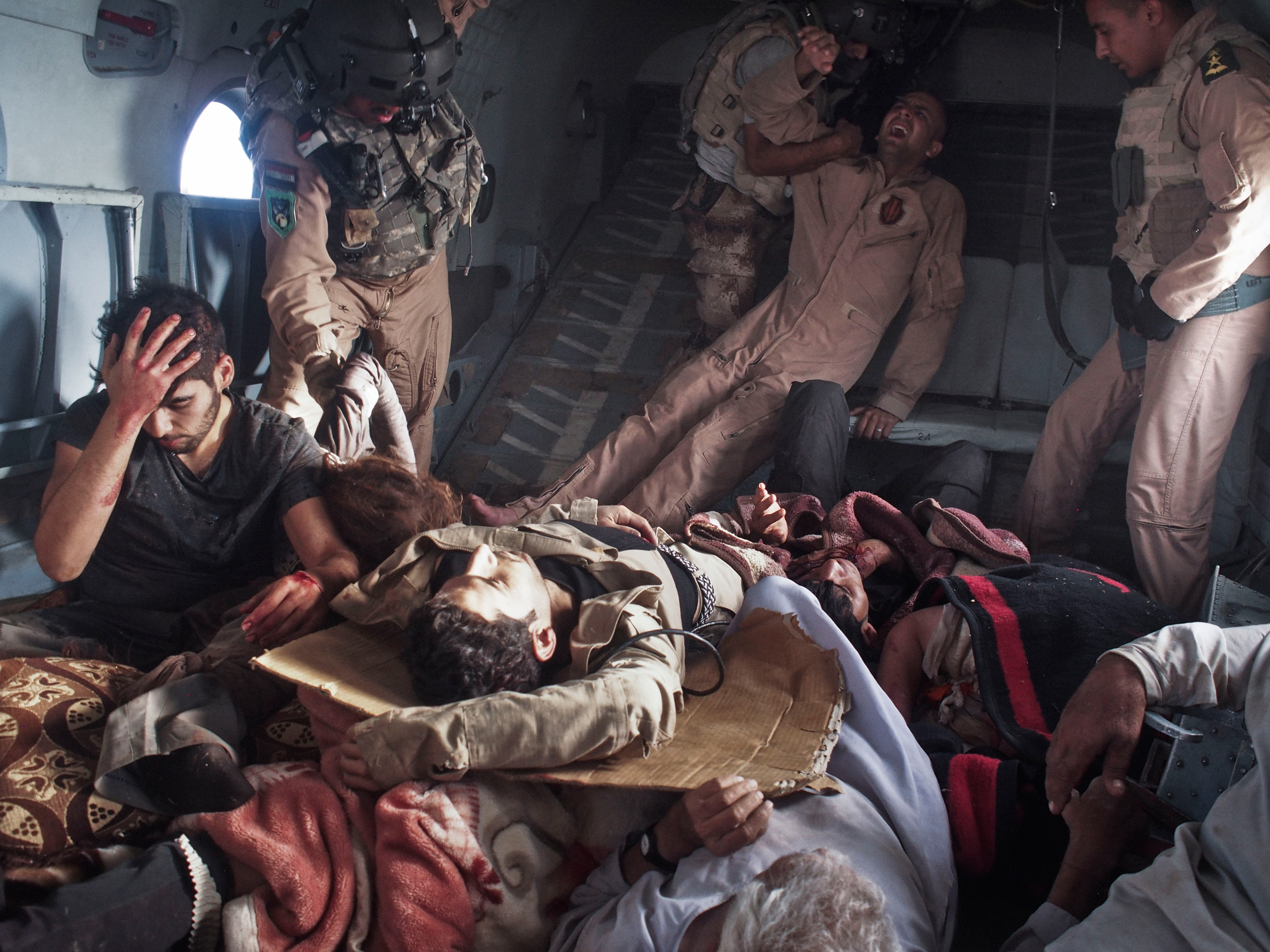 Injured survivors of an Iraqi Air Force helicopter crash on Mount Sinjar, Iraq lie onboard a rescue helicopter on its way to Iraqi Kurdistan on August 12, 2014. The survivors included Yazidi civilians, Kurdish and Iraqi Army personnel, and journalists. The Yazidis were fleeing persecution at the hands of Islamist extremists who had recently taken over their hometowns in Iraq's Ninevah province. In the high grounds of Mount Sinjar, thousands of Yazidis found safety from ISIS, but also the risk of dying from hunger and thirst. The first rescue helicopter had been sent to save the besieged civilians from that dismal fate, but it crashed into the side of the mountain shortly after takeoff.
