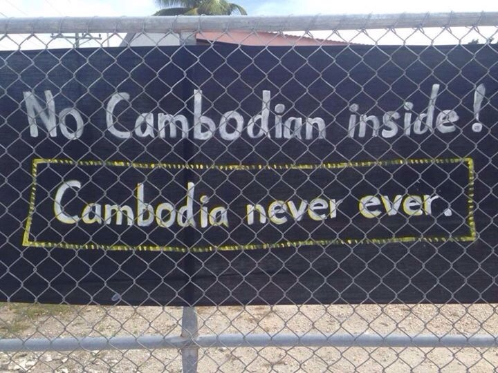 A banner fixed to a fence on Anibare Lodge, the main camp for refugee families on Nauru, reads  Cambodia, never, ever,  on March 7, 2015