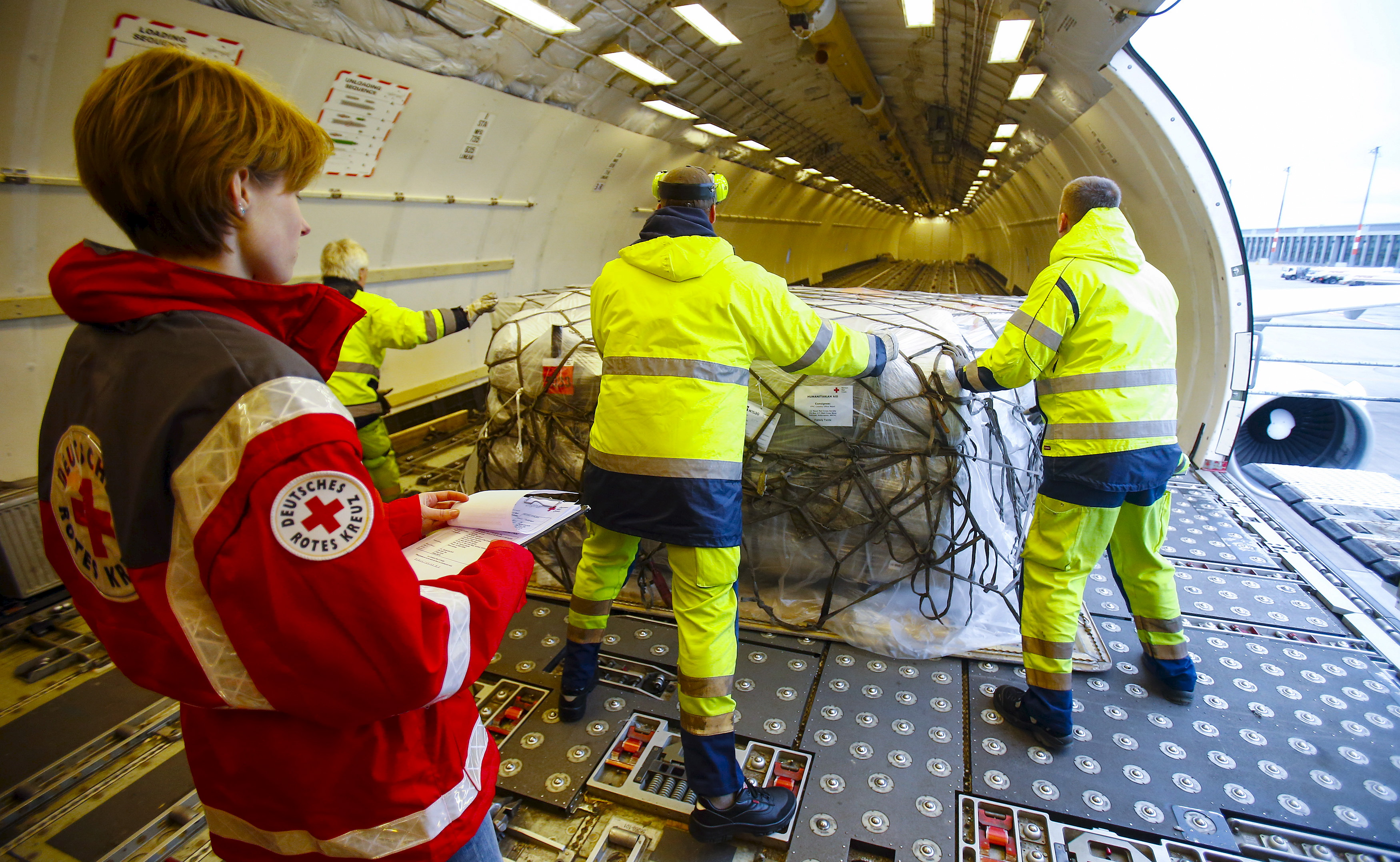 Workers load humanitarian aid from German Red Cross (DRK) for victims of the earthquake in Nepal, into an aircraft at Schoenefeld airport outside Berlin April 27, 2015.