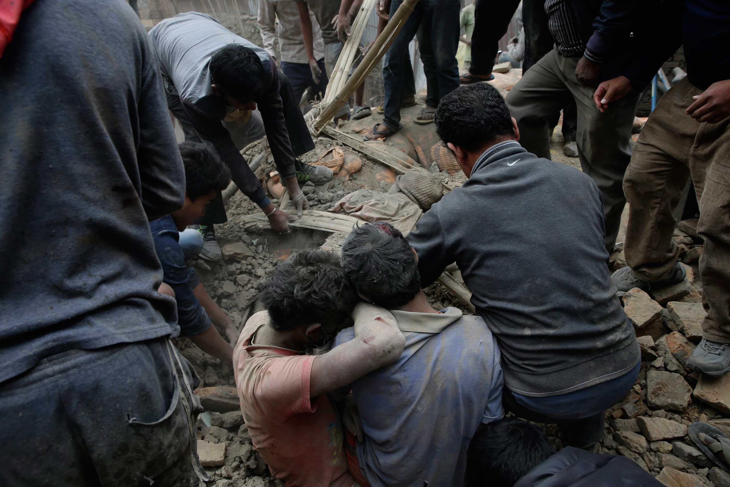People work to free a man trapped in debris in Kathmandu.