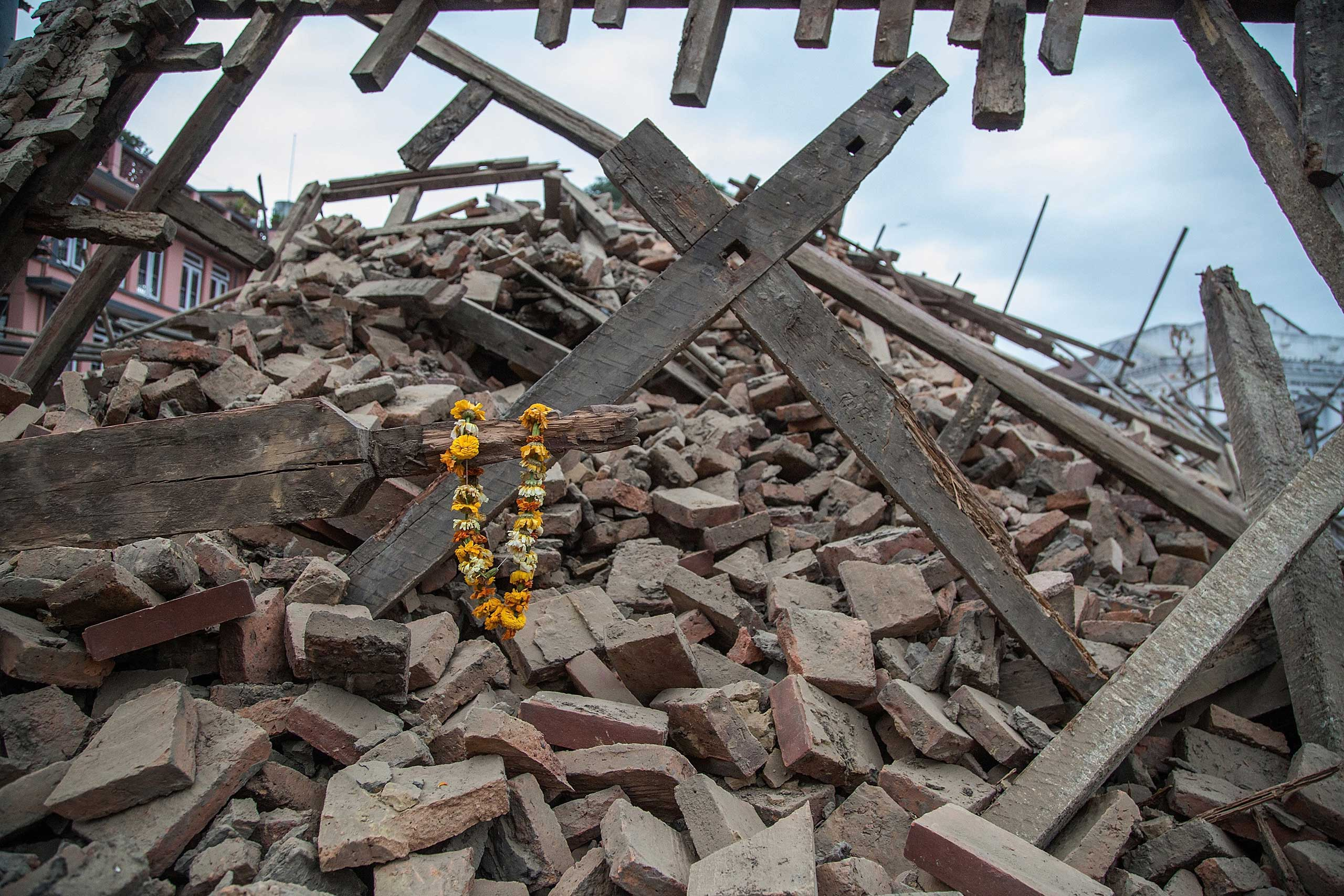 Flowers are left by survivors on top of debris from a collapsed building at Basantapur Durbar Square following an earthquake in Kathmandu on April 25, 2015.