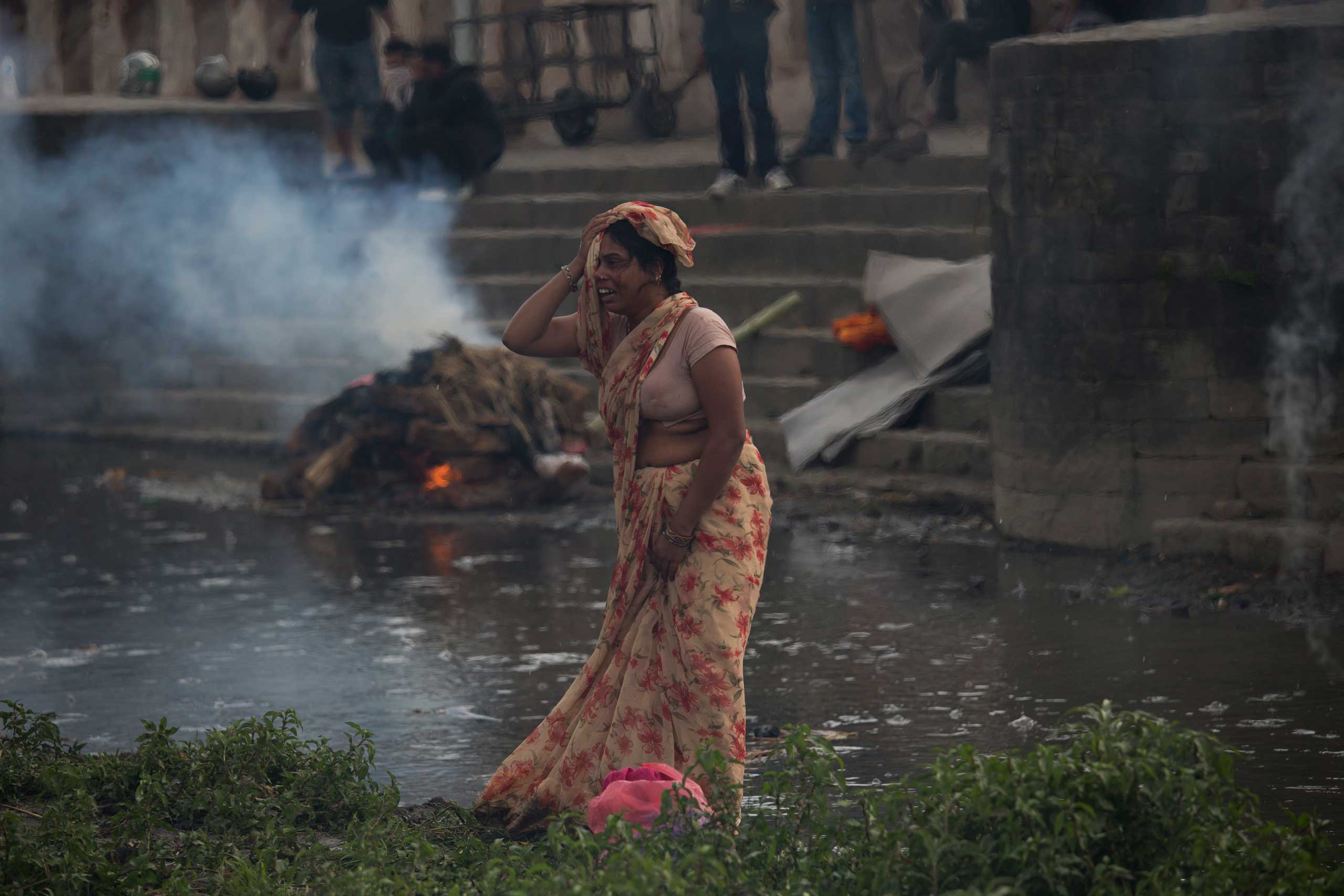 A woman weeps during the cremation of a victim of Saturday's earthquake, at the Pashupatinath temple, on the banks of Bagmati river, in Kathmandu on April 26, 2015.