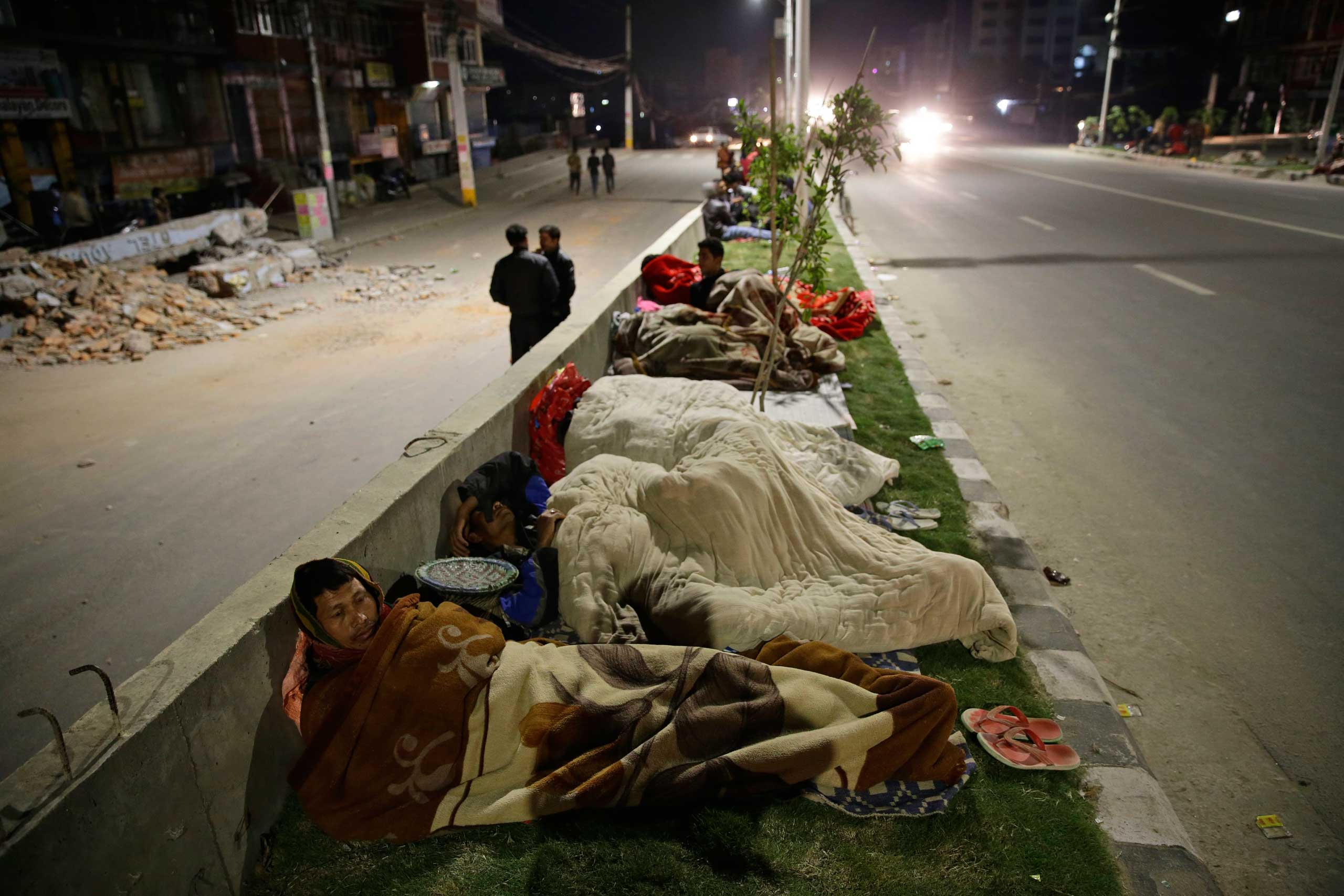 People sleep outside on a street following a massive earthquake in Kathmandu.