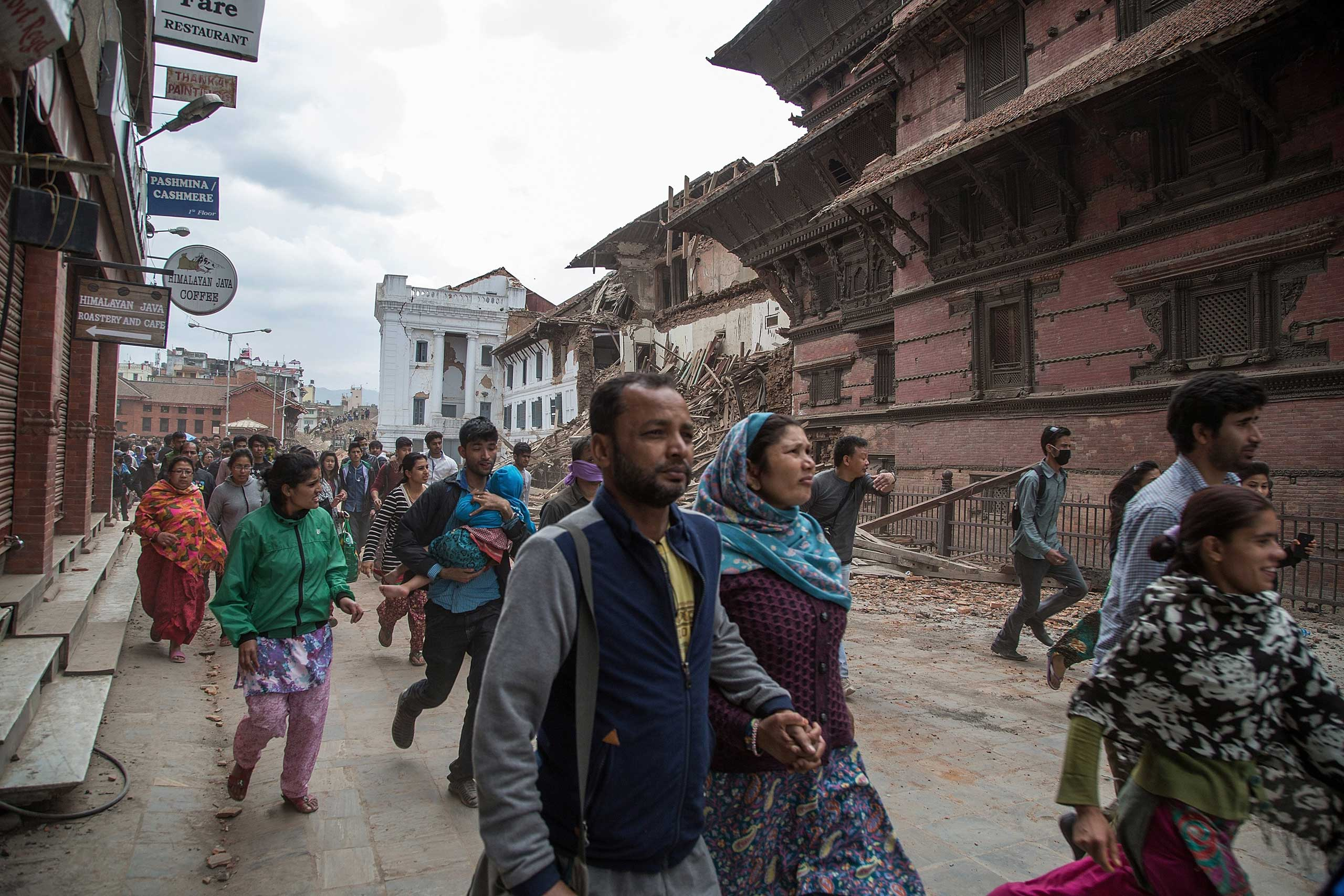 Residents run to shelters after an aftershock hit Kathmandu on April 25, 2015.