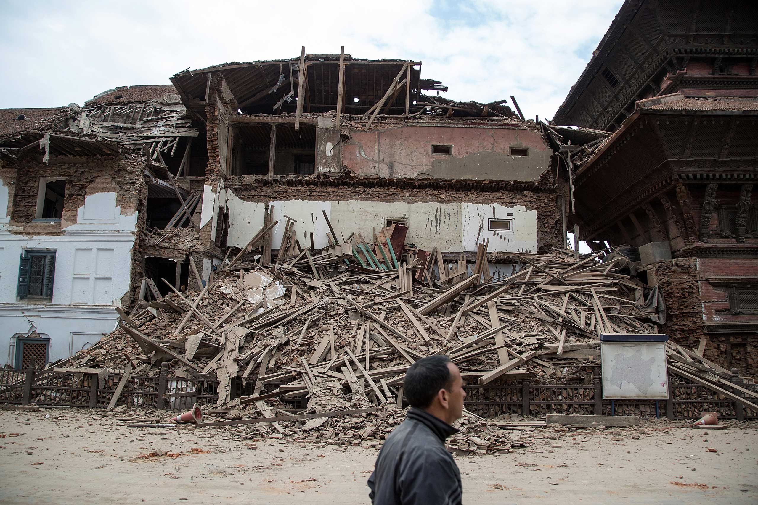 Resident passes in front of a collapsed temple at Basantapur Durbar Square in Kathmandu on April 25, 2015.