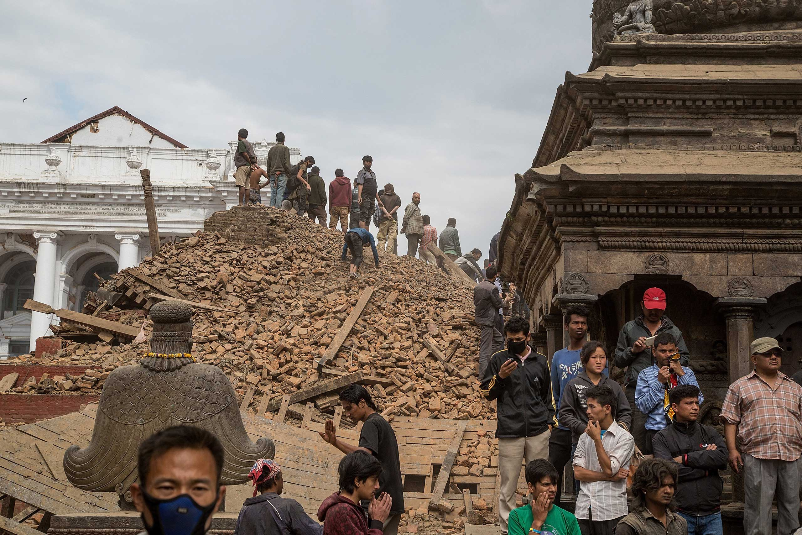 Emergency workers and bystanders clear debris while searching for survivors under a collapsed temple in Basantapur Durbar Square following an earthquake in Kathmandu on April 25, 2015.