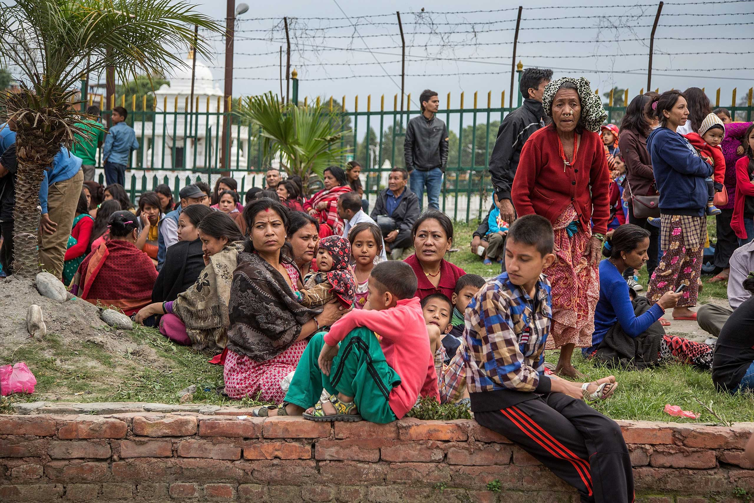 Residents sit in open spaces as aftershocks hit the city following an earthquake in Kathmandu on April 25, 2015.