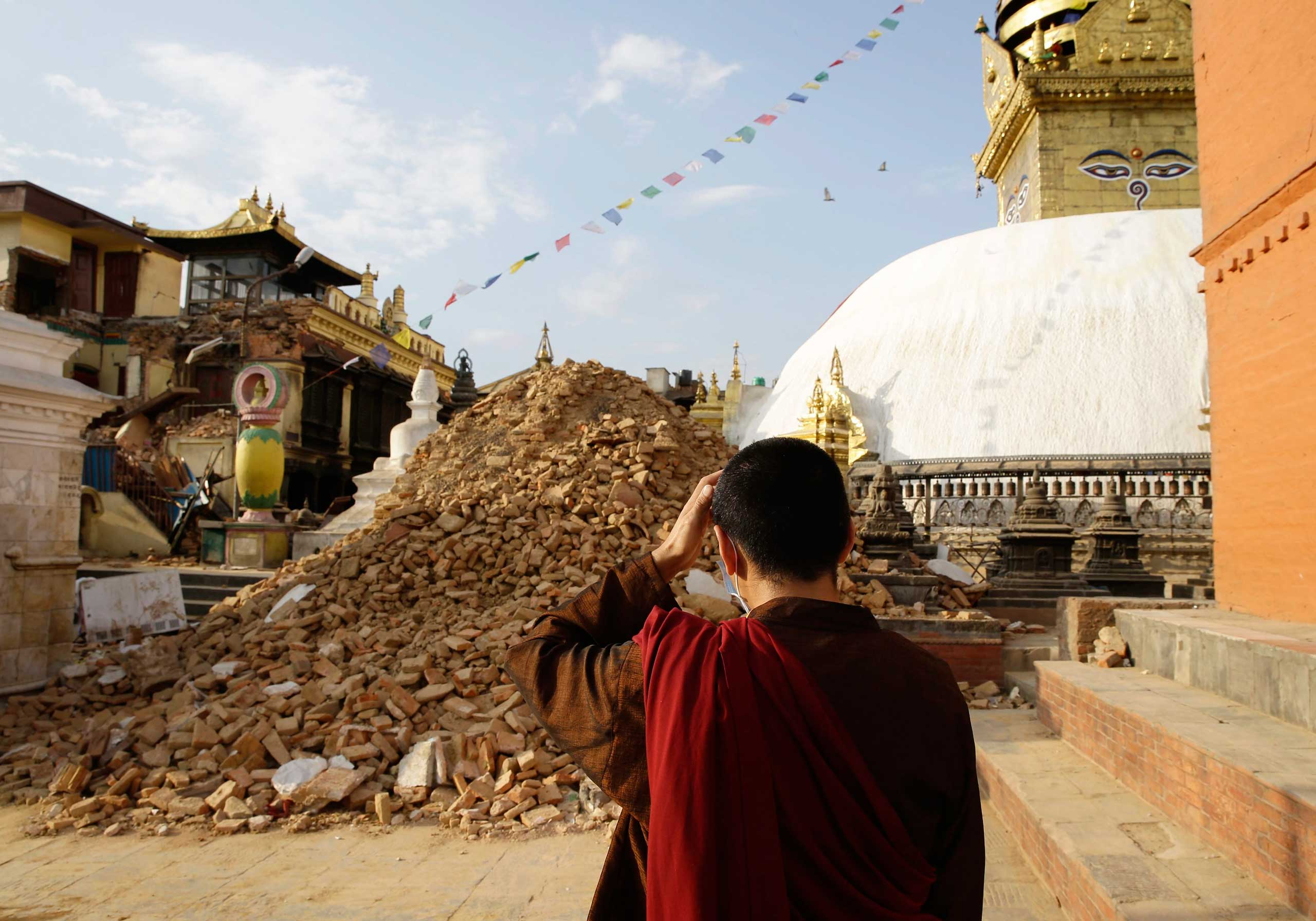 A monk inspects the damage at Nepalese heritage site Syambhunaath Stupa, also known as monkey temple, after a powerful earthquake struck Nepal, in Kathmandu on April 26, 2015.